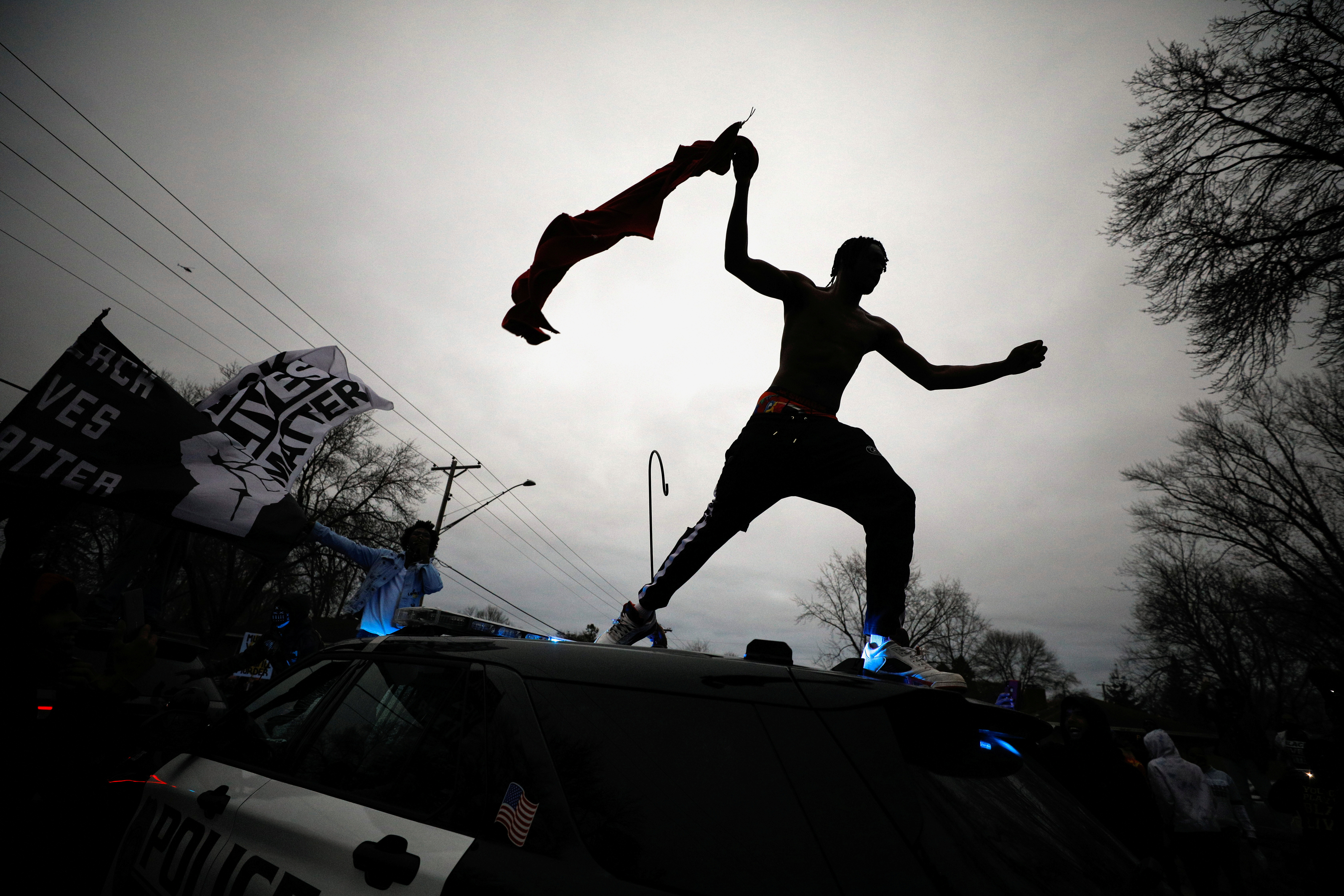 A demonstrator jumps off a police cruiser during a protest after police allegedly shot and killed a man, who local media report is identified by the victim's mother as Daunte Wright, in Brooklyn Center, Minnesota, U.S., April 11, 2021. REUTERS/Nick Pfosi     T