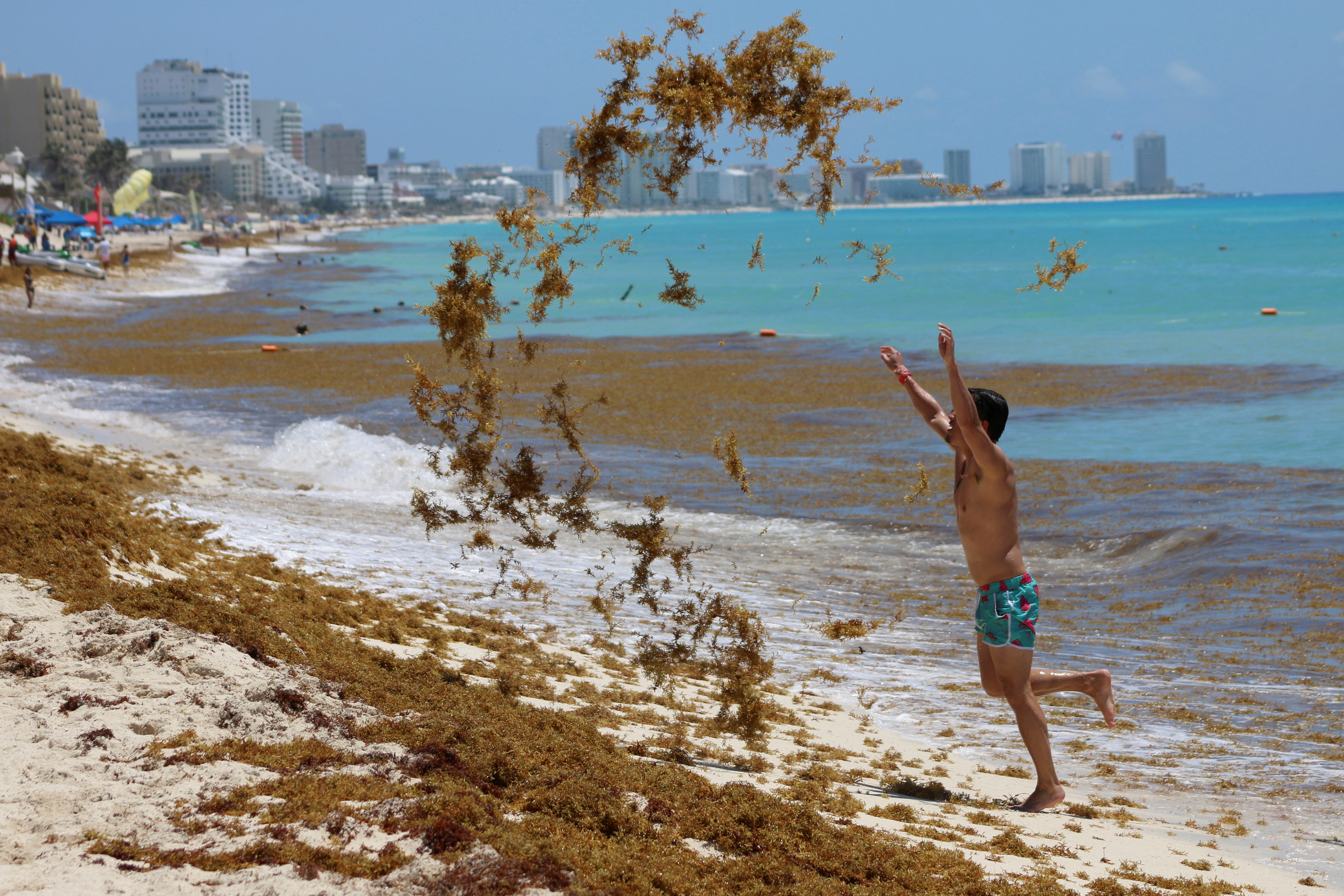 A tourist tosses sargassum into the air at Marlin Beach in Cancun, Mexico May 30, 2021. REUTERS/Paola Chiomante