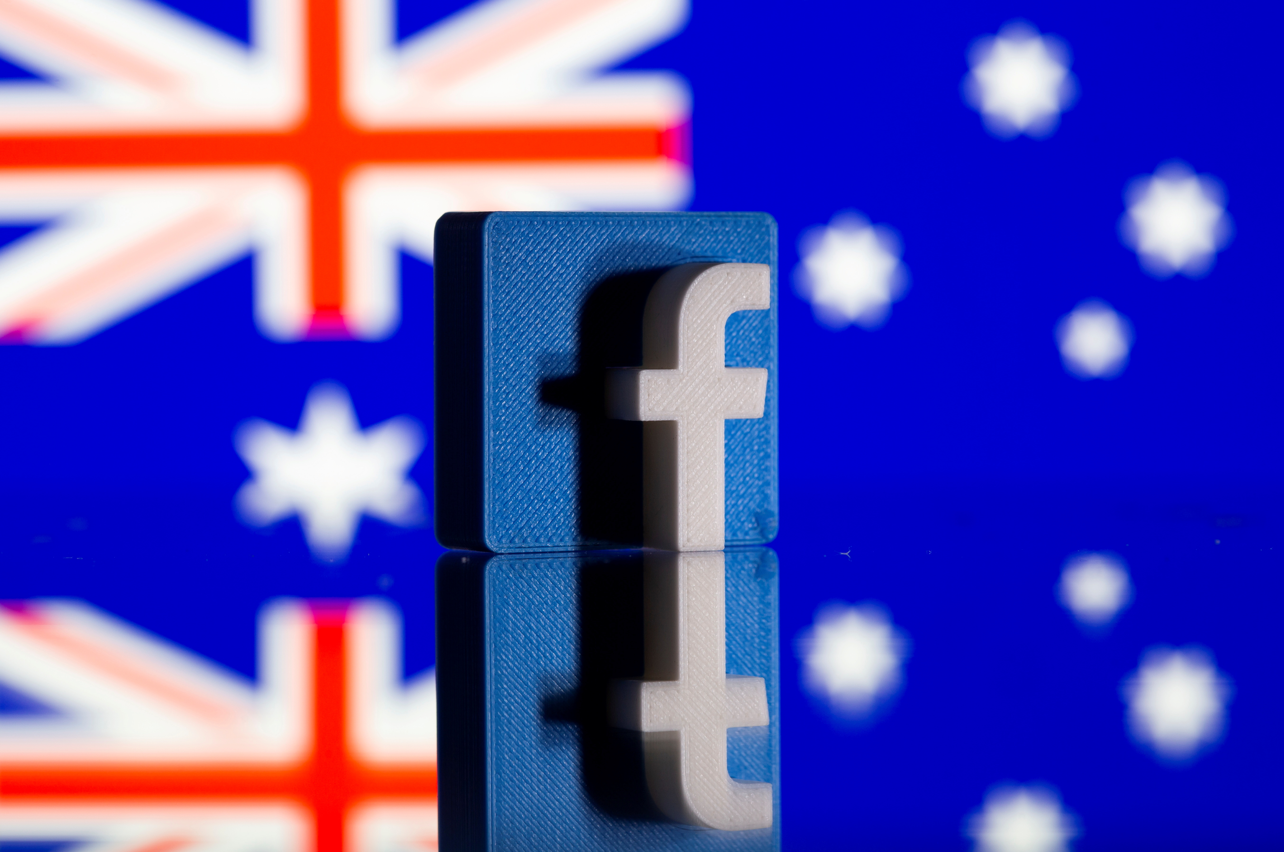 A 3D-printed Facebook logo is seen in front of a displayed Australian flag in this illustration photo taken February 18, 2021. REUTERS/Dado Ruvic/Illustration/File Photo