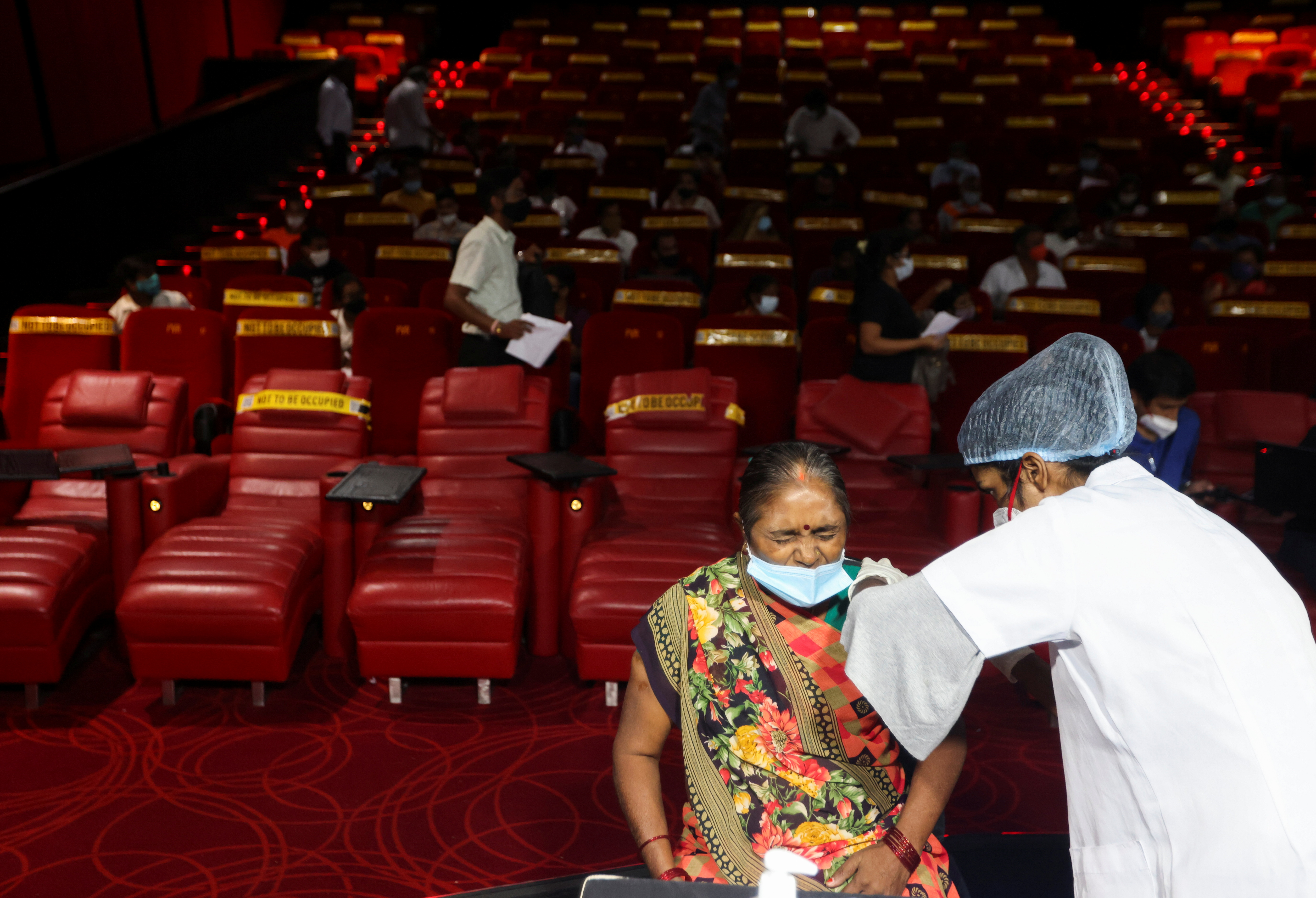 A woman reacts as she receives a dose of COVISHIELD, a vaccine against coronavirus disease (COVID-19) manufactured by Serum Institute of India, at a cinema hall in Mumbai, India, August 17, 2021. REUTERS/Francis Mascarenhas