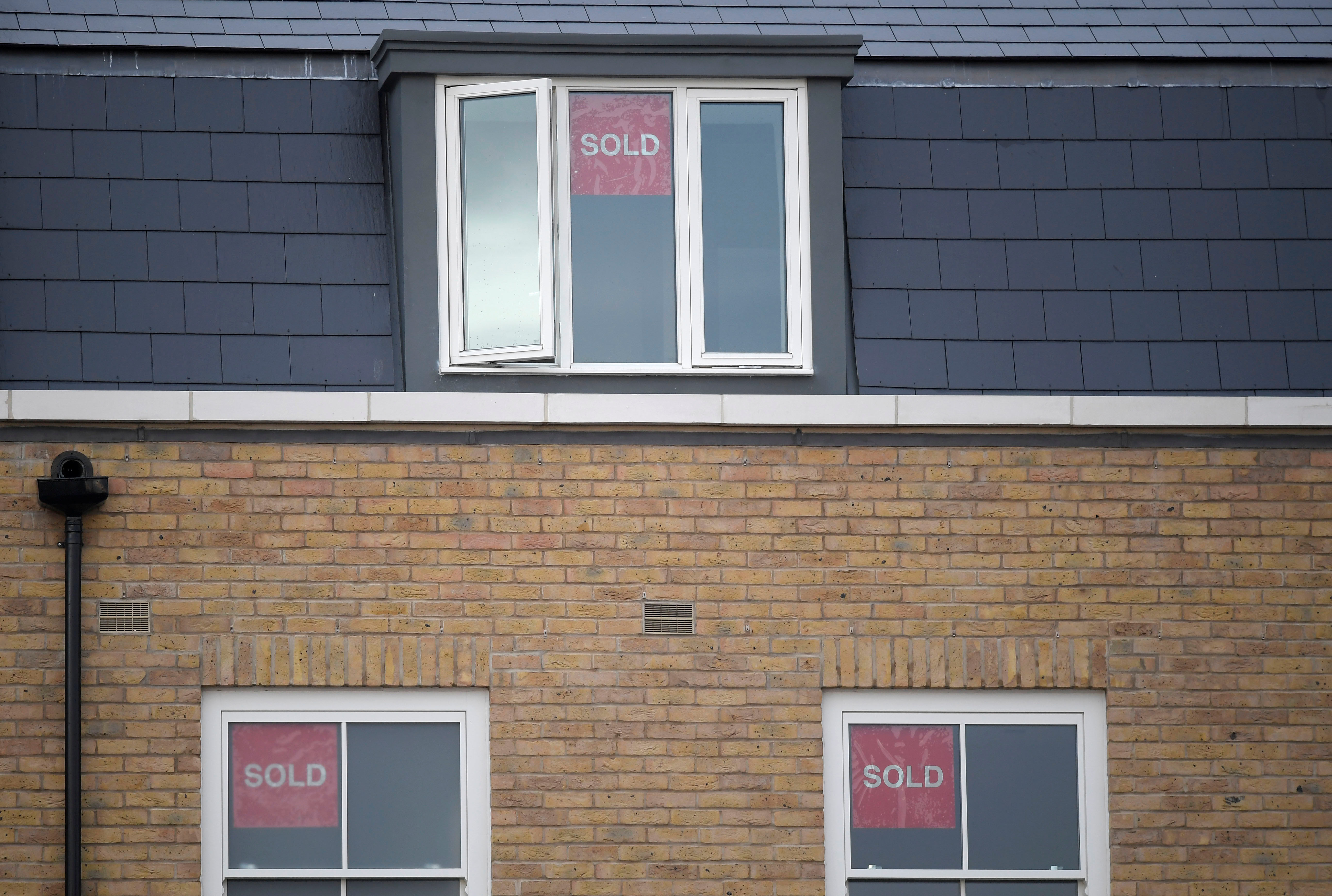 Property sold signs are seen on windows of a group of newly built houses in west London, Britain, November 23, 2017. REUTERS/Toby Melville/Files