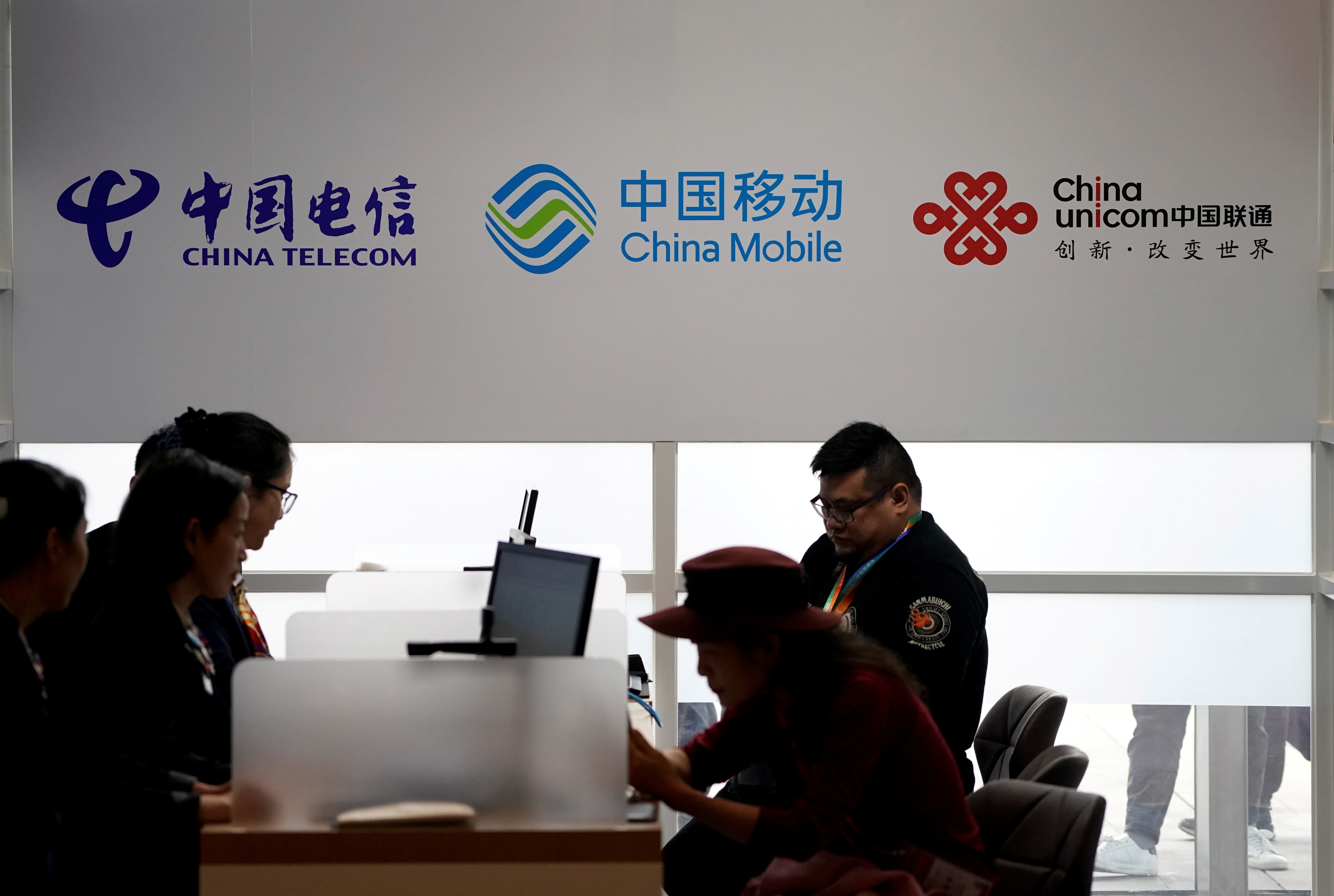 Signs of China Telecom, China Mobile and China Unicom are seen during the China International Import Expo (CIIE) at the National Exhibition and Convention Center in Shanghai, China, Nov. 5, 2018. REUTERS/Aly Song