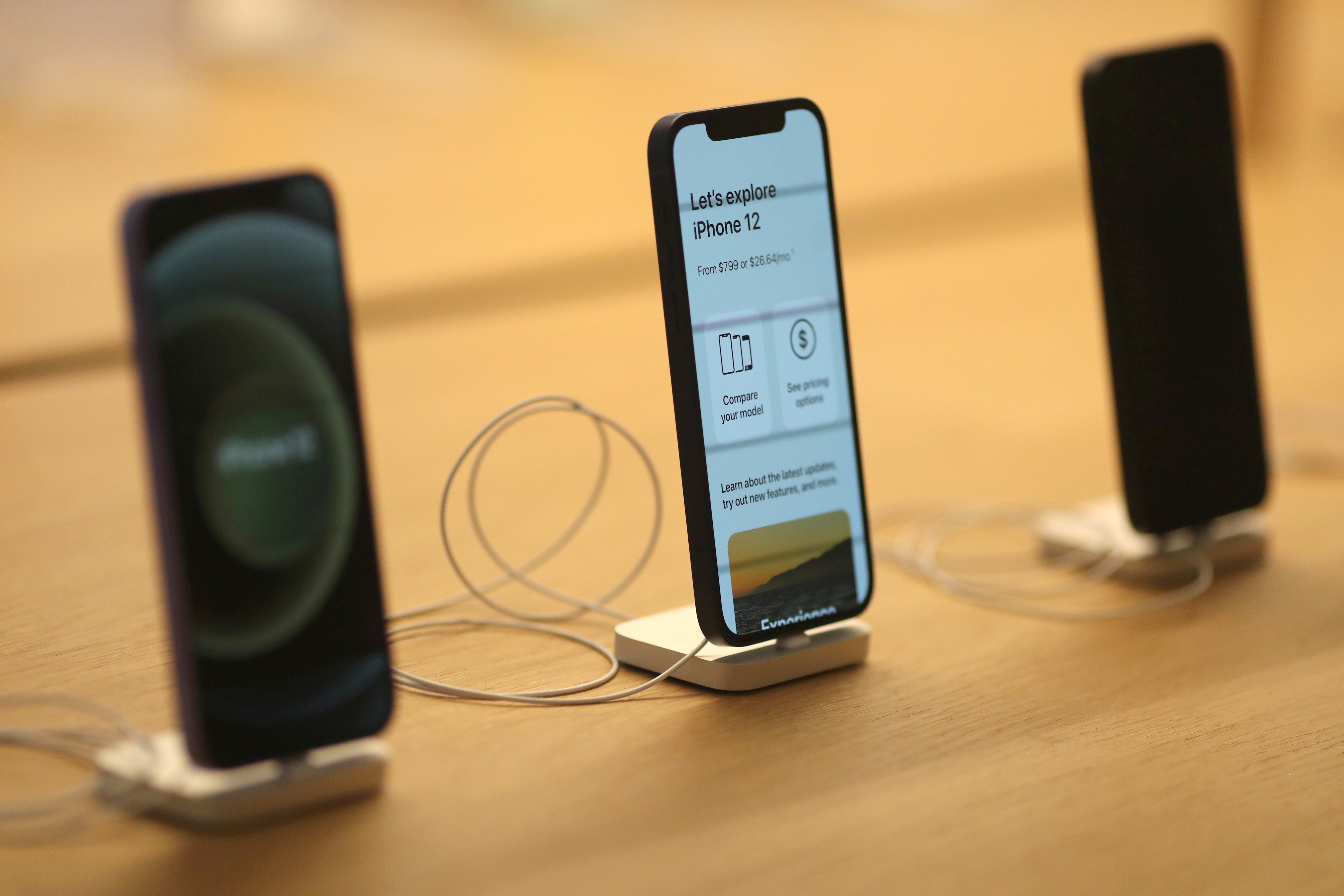 IPhone 12 phones are seen at the new Apple Store on Broadway in downtown Los Angeles, California, U.S., June 24, 2021. REUTERS/Lucy Nicholson/File Photo