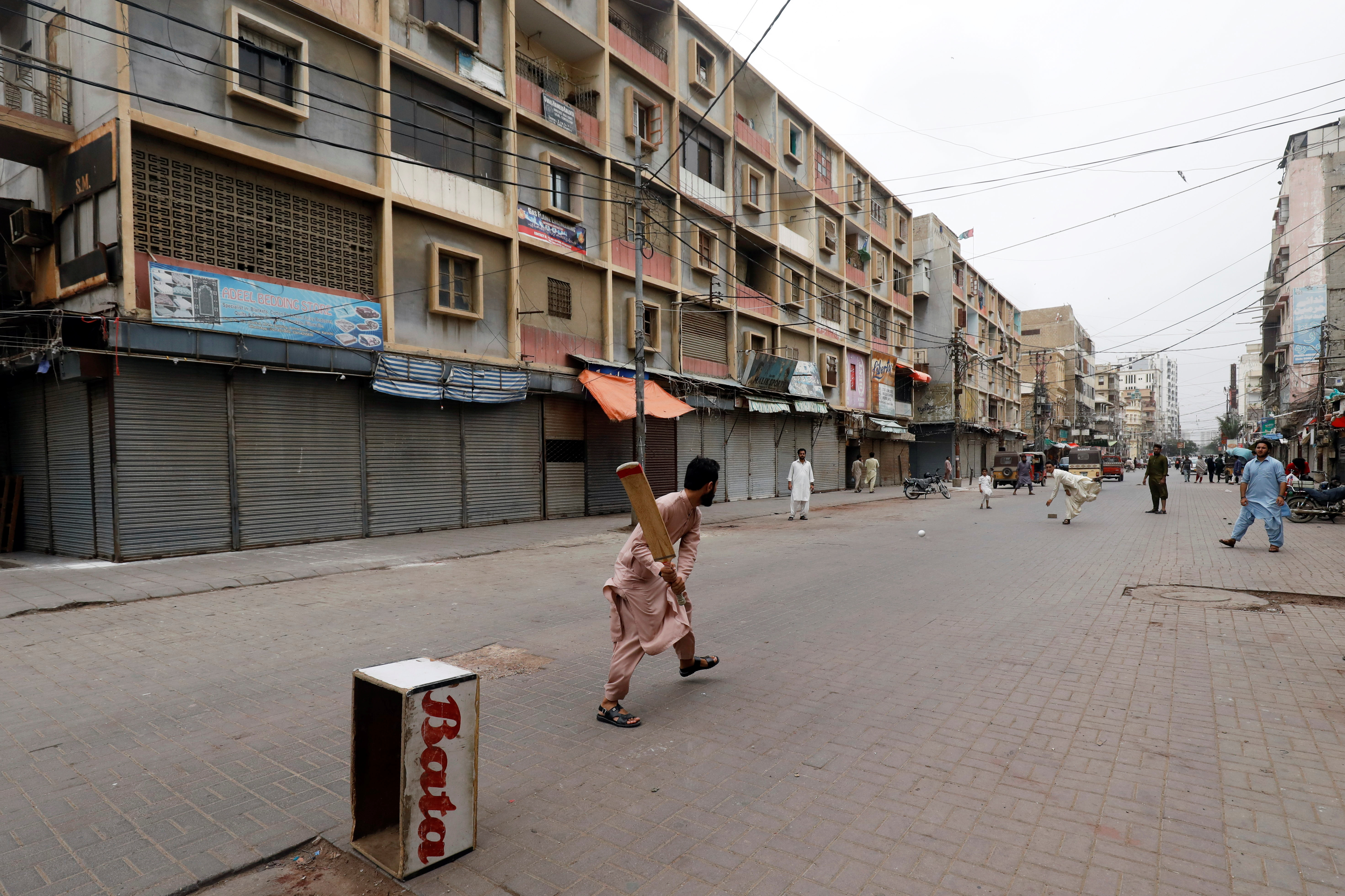 Shopkeepers play cricket along closed market during a partial lockdown after Sindh provincial government decided to shut markets, restaurants, public beaches and discouraged large gatherings to curb the outbreak of the coronavirus disease (COVID-19), in Karachi, Pakistan July 30, 2021. REUTERS/Akhtar Soomro