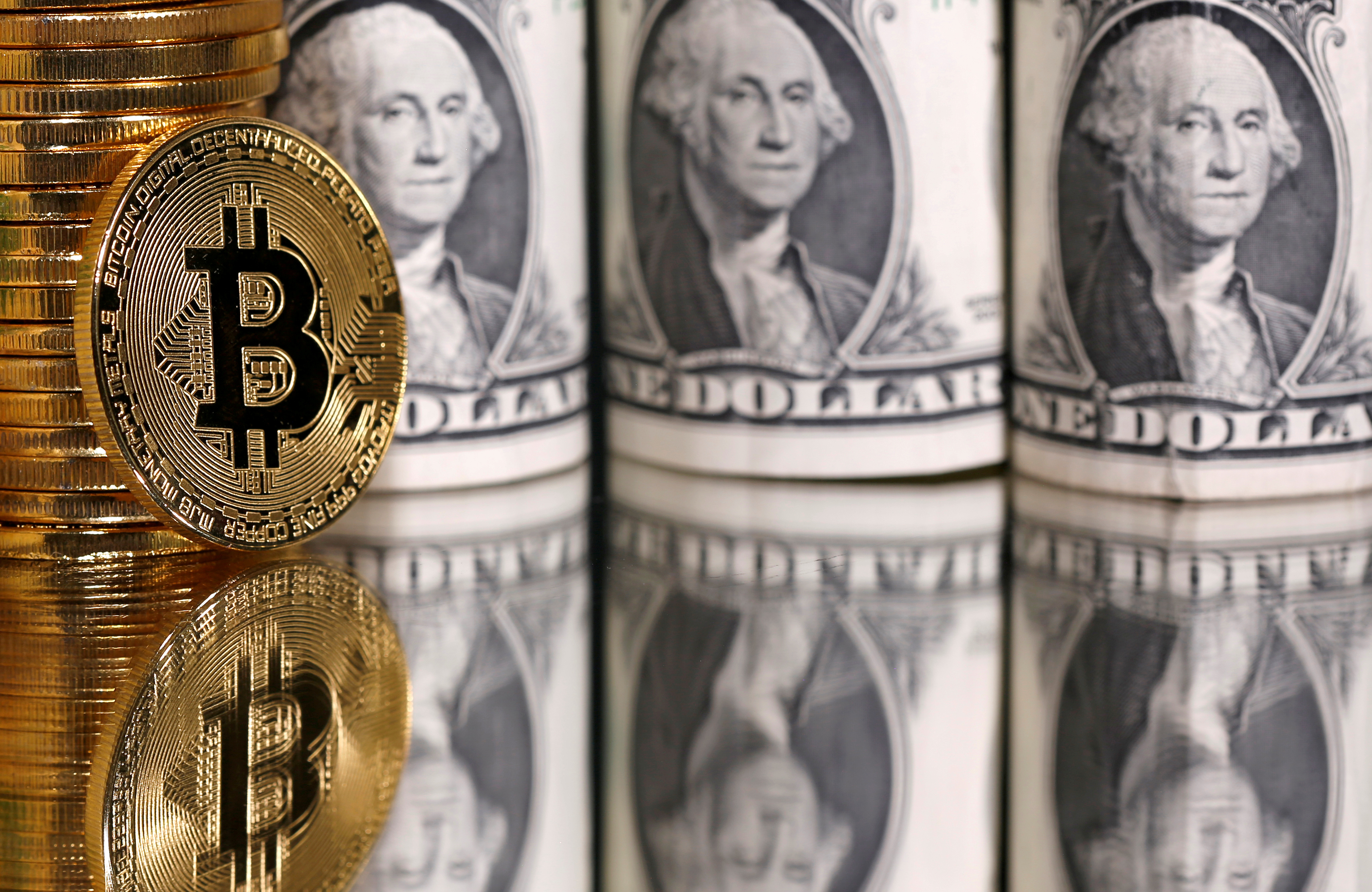Representations of bitcoin and U.S. dollar banknotes are seen in this illustration taken January 6, 2020. REUTERS/Dado Ruvic/Illustration