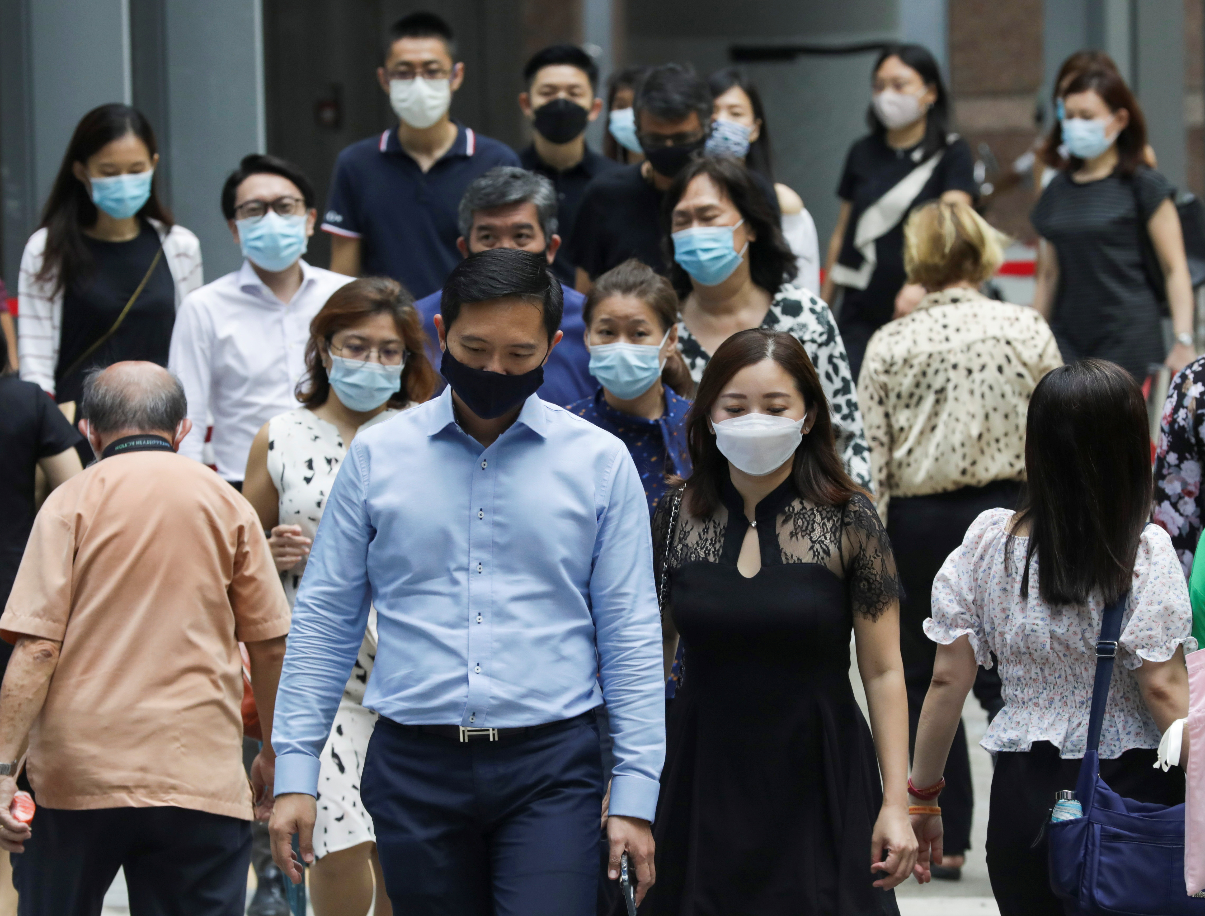 Office workers wearing masks cross a street during lunch hour, amid the coronavirus disease (COVID-19) outbreak, in Singapore May 12, 2021.   REUTERS/Dawn Chua