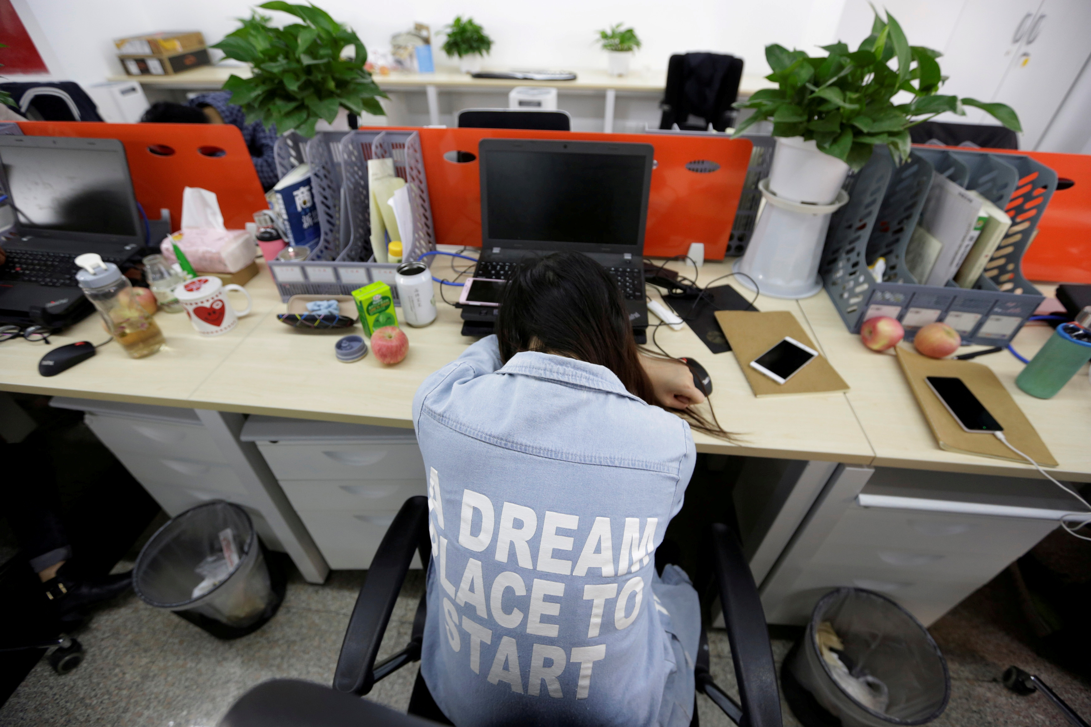Yang Juan, an employee at Goopal Group, takes a nap in her seat after lunch, in Beijing, China, April 21, 2016. Office workers sleeping on the job is a common sight in China where workers often burn the midnight oil to meet deadlines and compete with their rivals. REUTERS/Jason Lee/File Photo