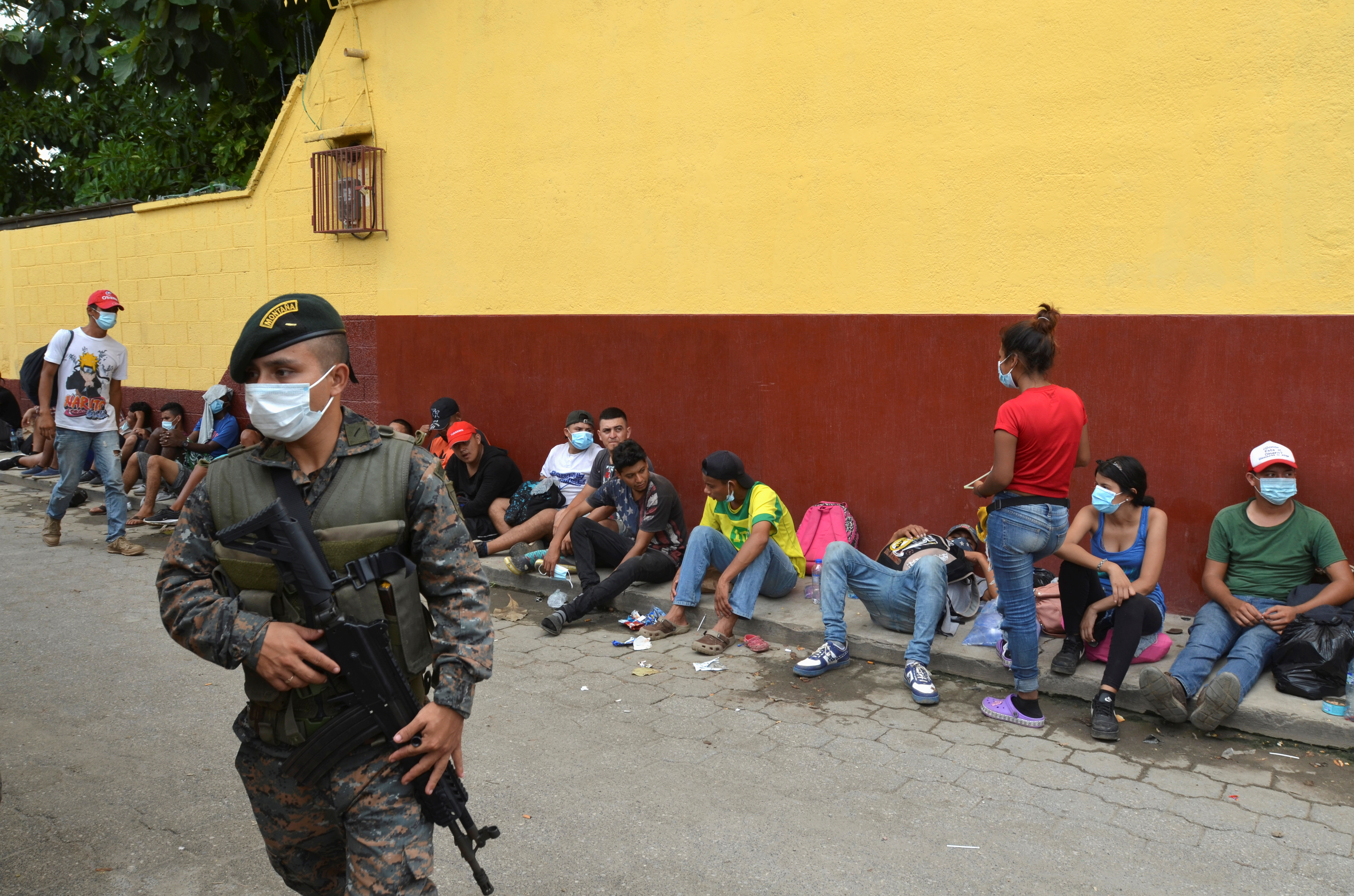 A Guatemalan soldier patrols to prevent a group of Honduran migrants who are trying to reach the U.S. , from moving towards the Guatemala and Mexico border, as they sit outside the migrant shelter, in Tecun Uman, Guatemala October 3, 2020. REUTERS/Jose Torres