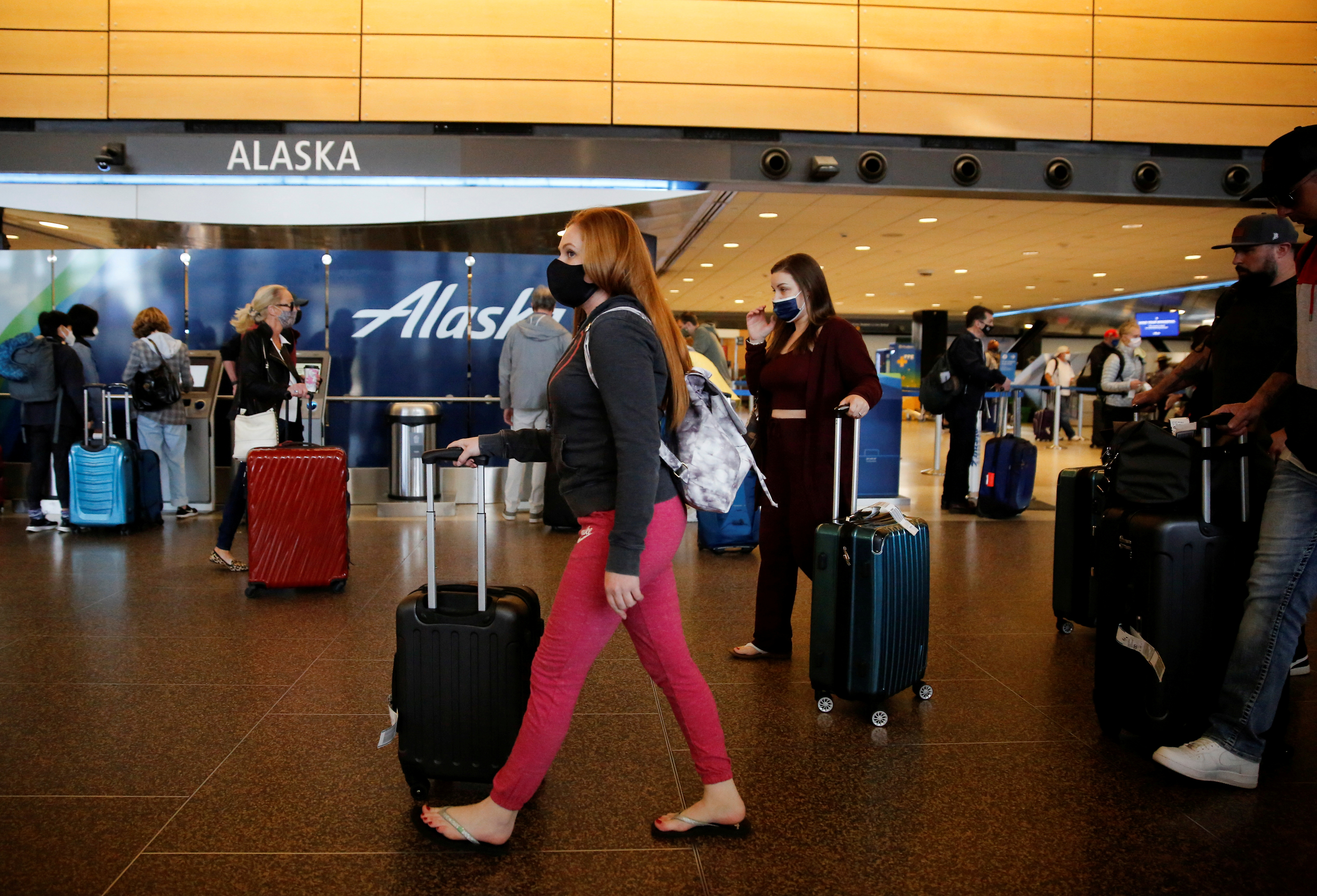 Travelers walk by check-in kiosks for Alaska Airlines at the departures section of Seattle-Tacoma International Airport in SeaTac, Washington, U.S. April 12, 2021.  REUTERS/Lindsey Wasson/File Photo