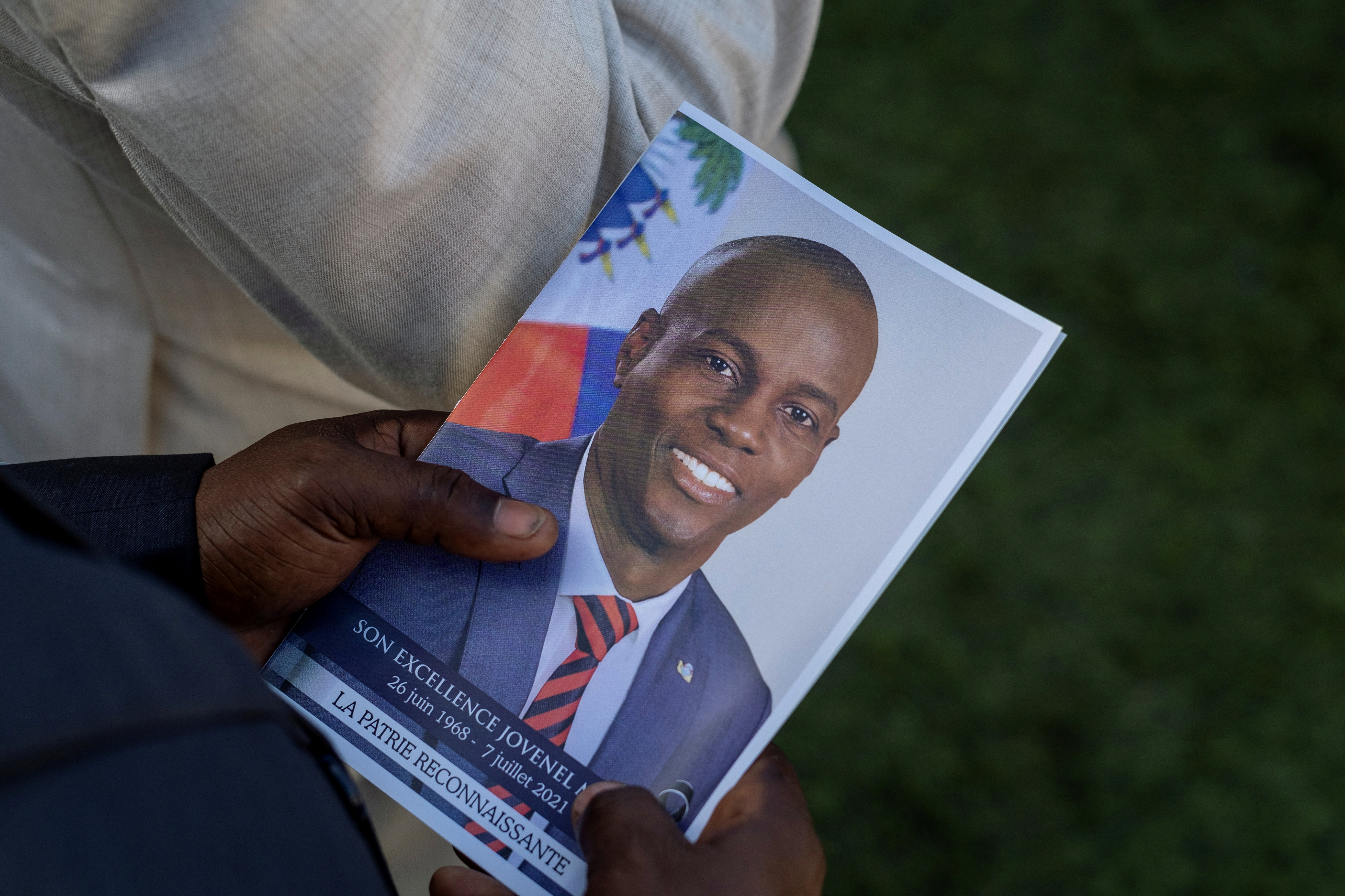 A person holds a photo of late Haitian President Jovenel Moise, who was shot dead earlier this month, during his funeral at his family home in Cap-Haitien, Haiti, July 23, 2021. REUTERS/Ricardo Arduengo