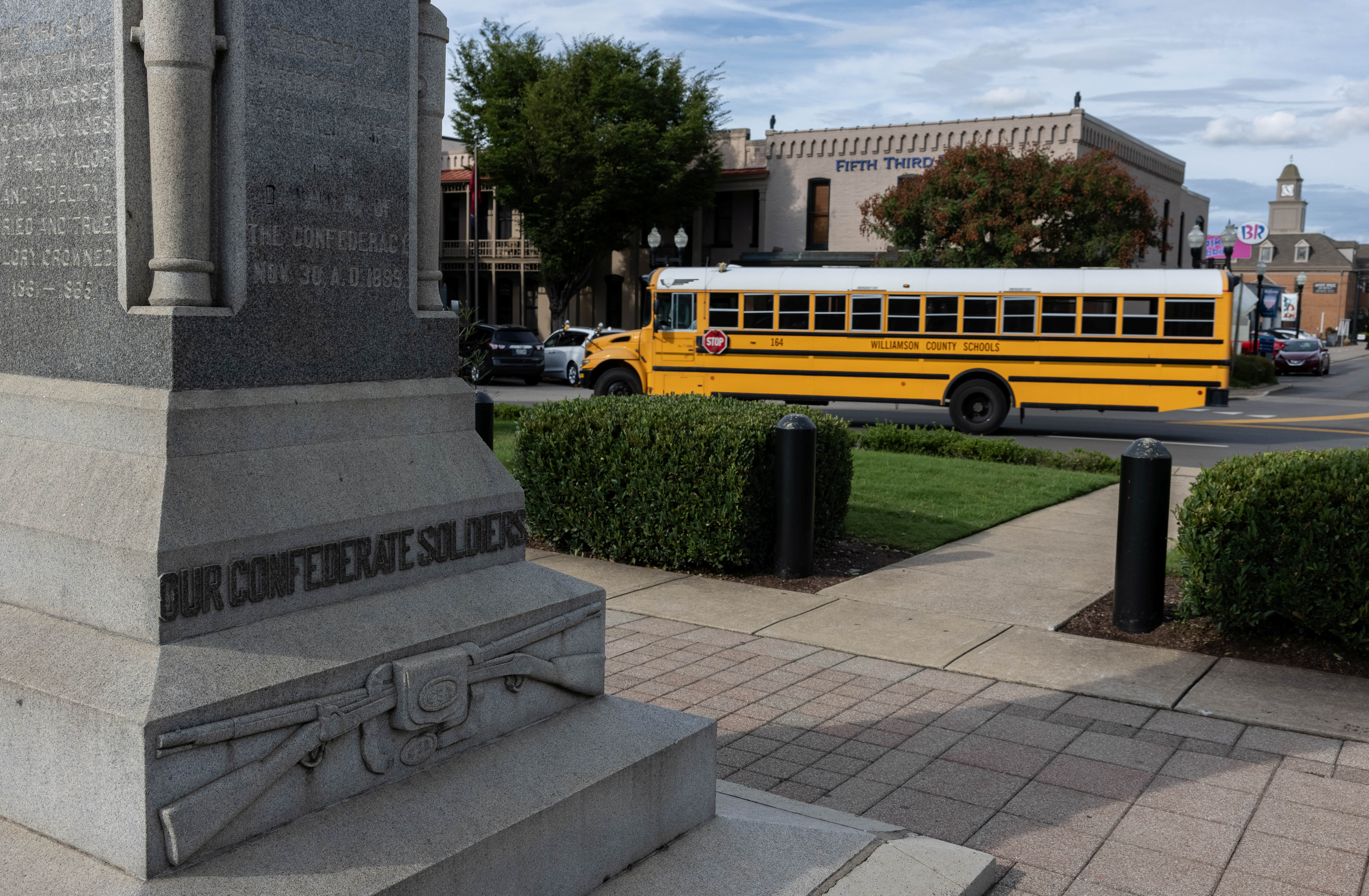 A Williamson County School bus drives past the Confederate monument which stands in the center of the town square in Franklin, Tennessee, U.S., atop the former slave market which operated in the mid-19th century and commemorates the Confederate soldiers who died in the battle of Franklin during the Civil War, August 17, 2021. Picture taken August 17, 2021. REUTERS/Evelyn Hockstein