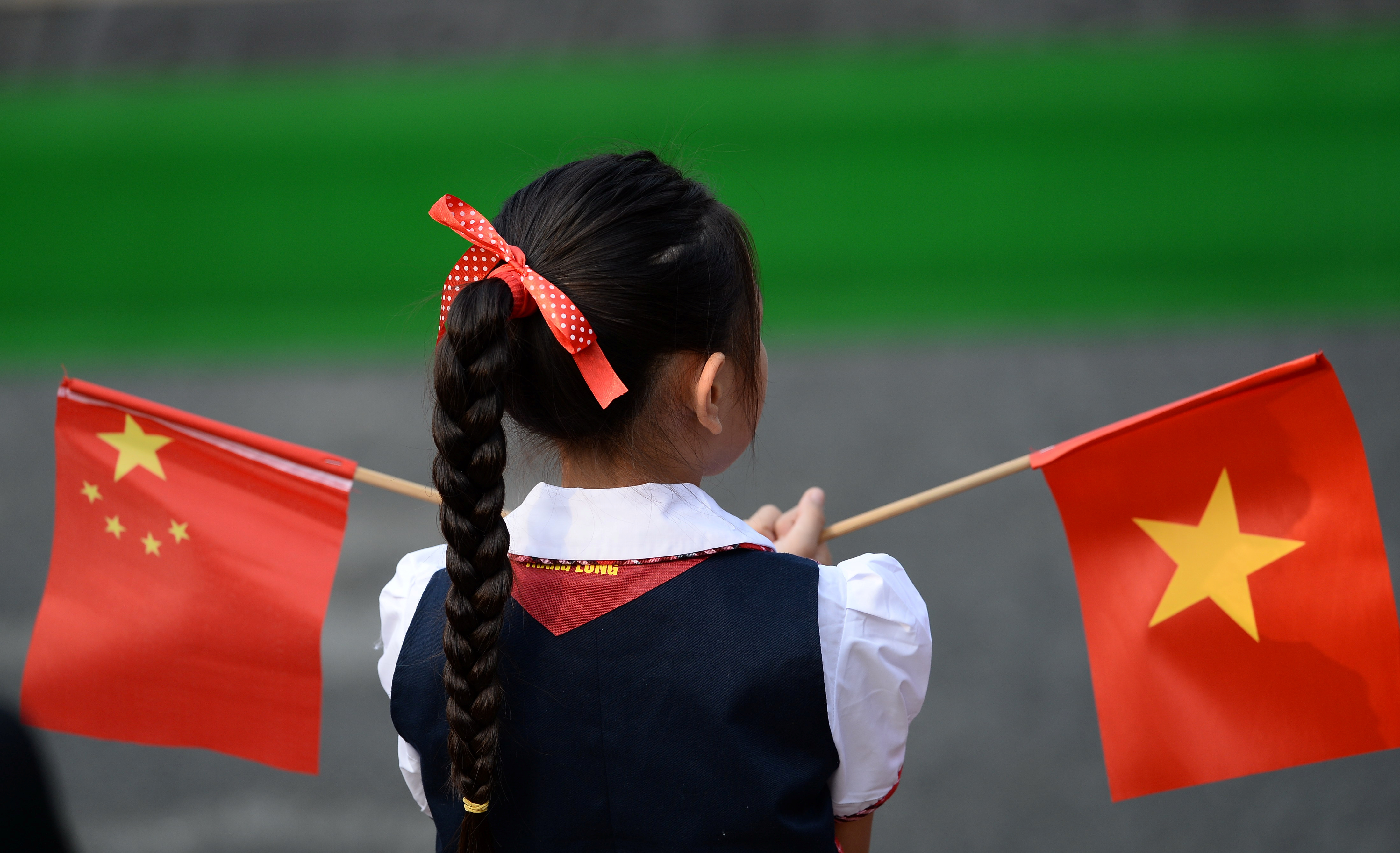 A Vietnamese pupil holds Vietnamese and Chinese flags before the welcoming ceremony at the Presidential Palace in Hanoi, Vietnam November 12, 2017. REUTERS/Hoang Dinh Nam/Pool