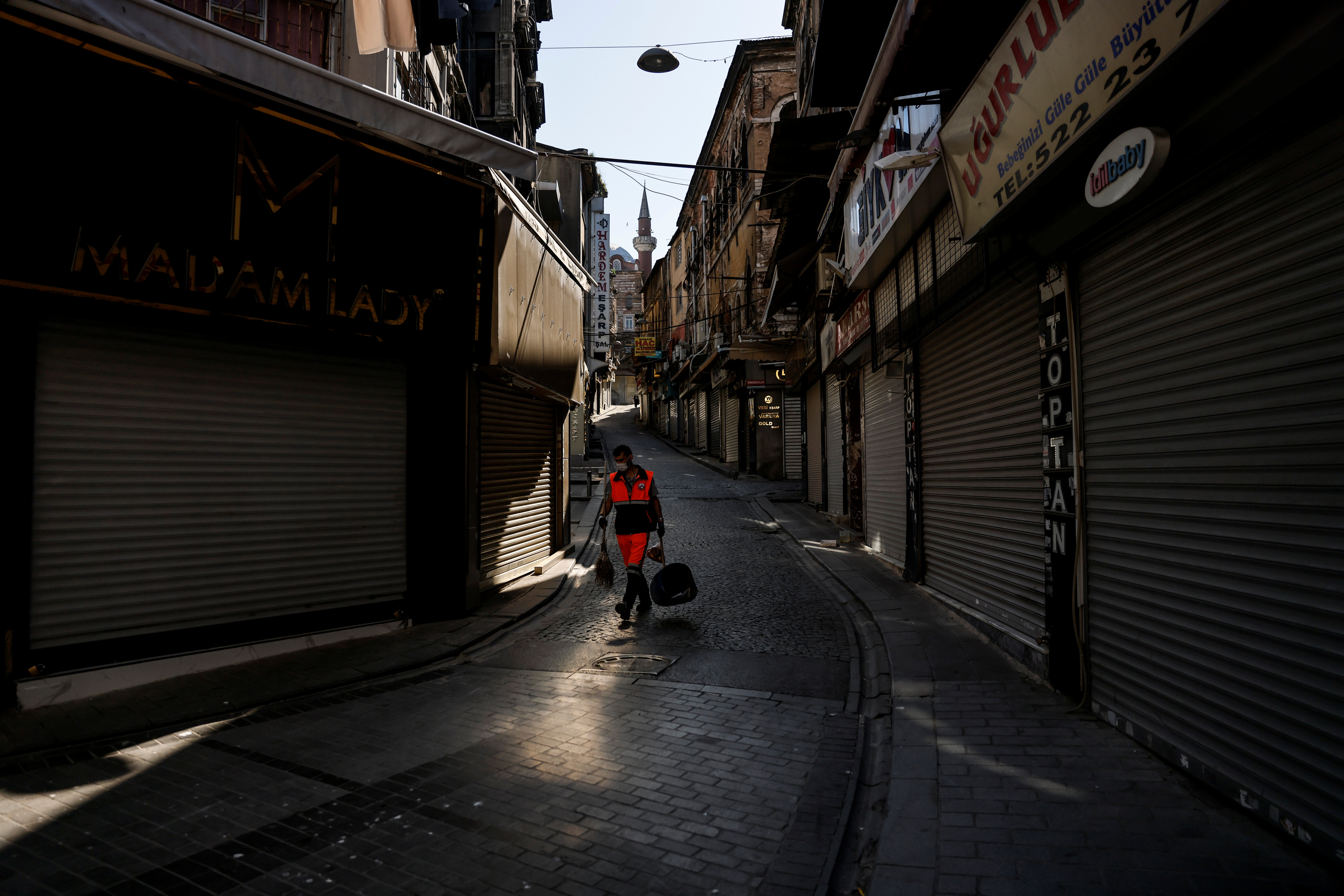 A municipality worker sweeps a street at Eminonu district in Istanbul, Turkey, during a nationwide lockdown imposed to slow the spread of the coronavirus disease (COVID-19), May 5, 2021. REUTERS/Umit Bektas