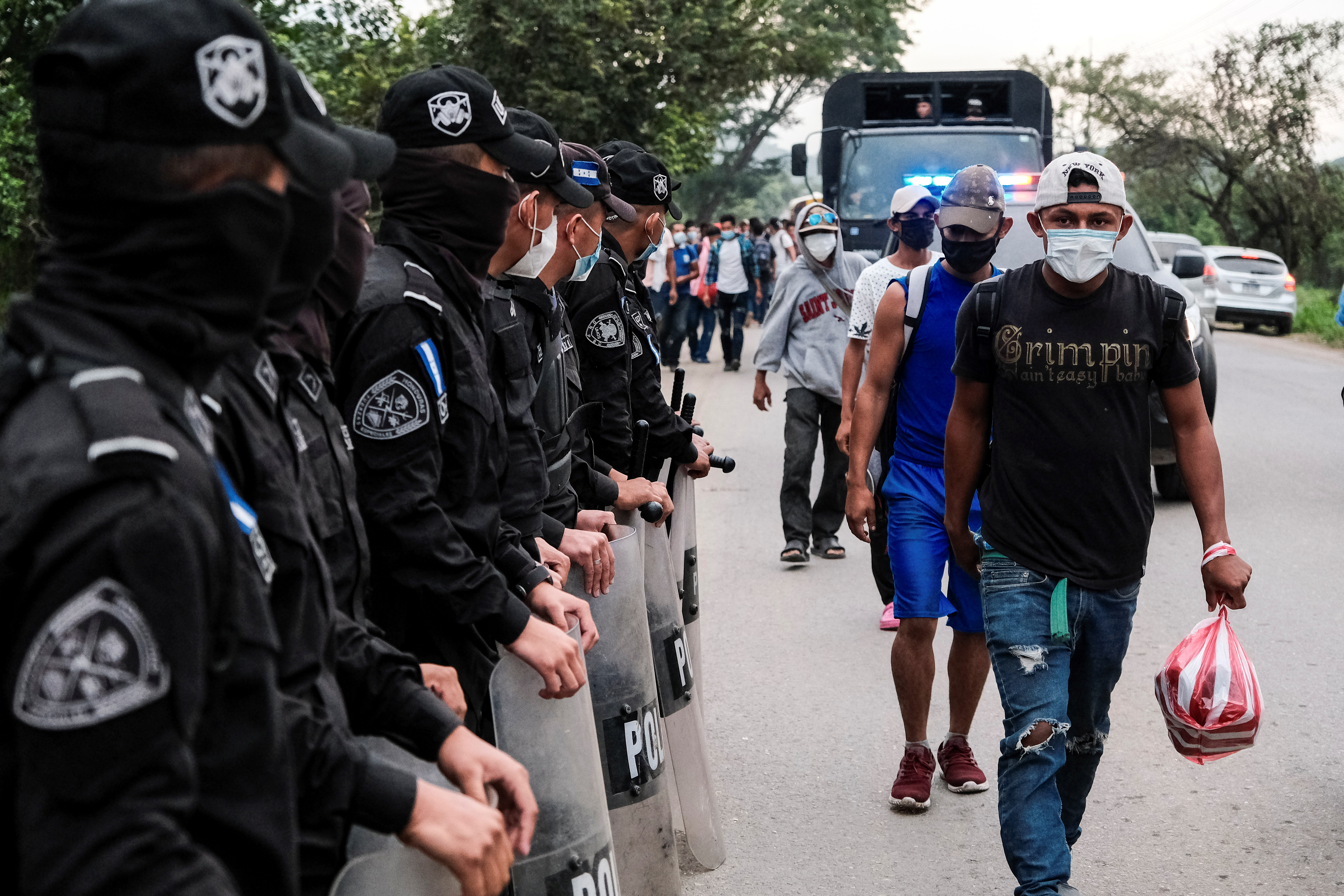 Hondurans walk past police officers at a police checkpoint in a new caravan of migrants, set to head to the United States, in Cofradia, Honduras January 15, 2021. REUTERS/Yoseph Amaya