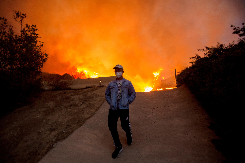 A man walks away from the Blue Ridge Fire burning in Yorba Linda, California, U.S., October 26, 2020. REUTERS/Ringo Chiu