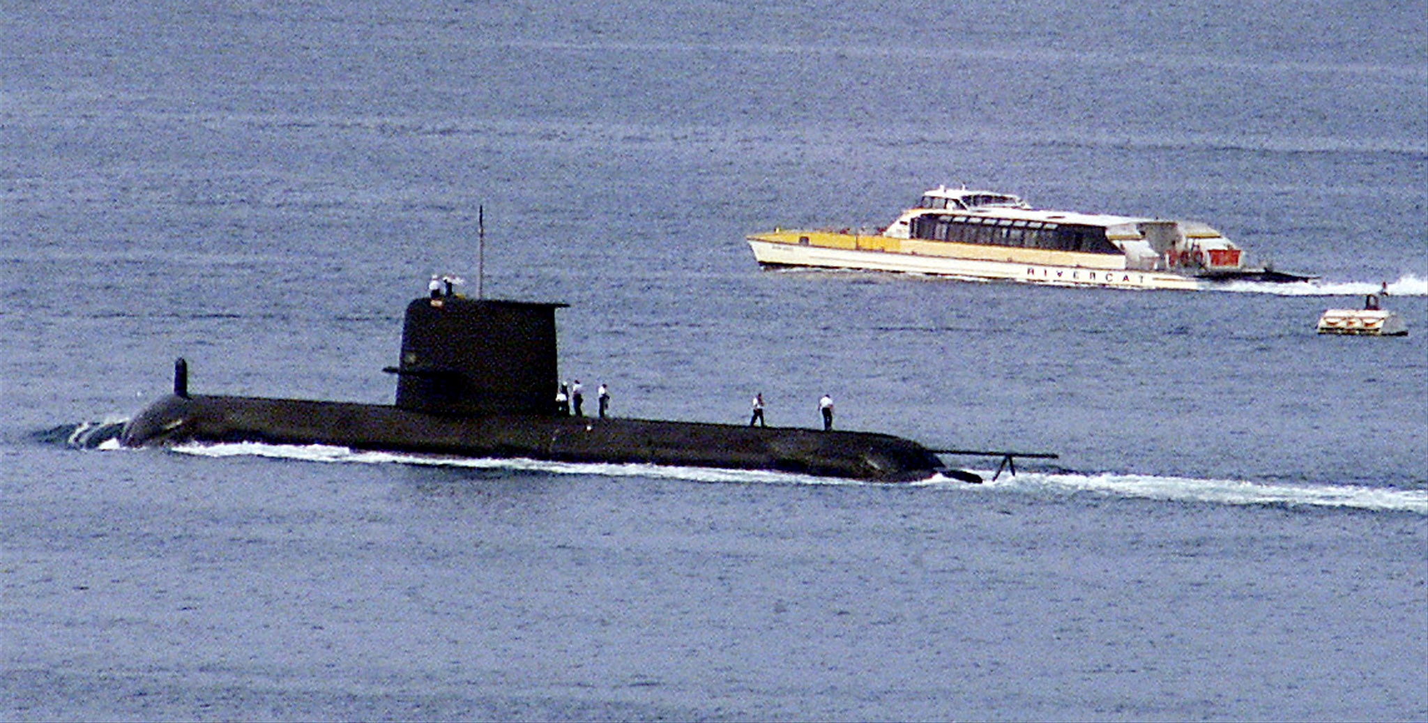 (File Photo) A Rivercat ferry passes by the Royal Australian Navy's Collins-class submarine HMAS Waller as it leaves Sydney Harbour on May 4, 2020. The Australian government has considered extending the life of the Collins class as it examines the fate of its next-generation sub program.