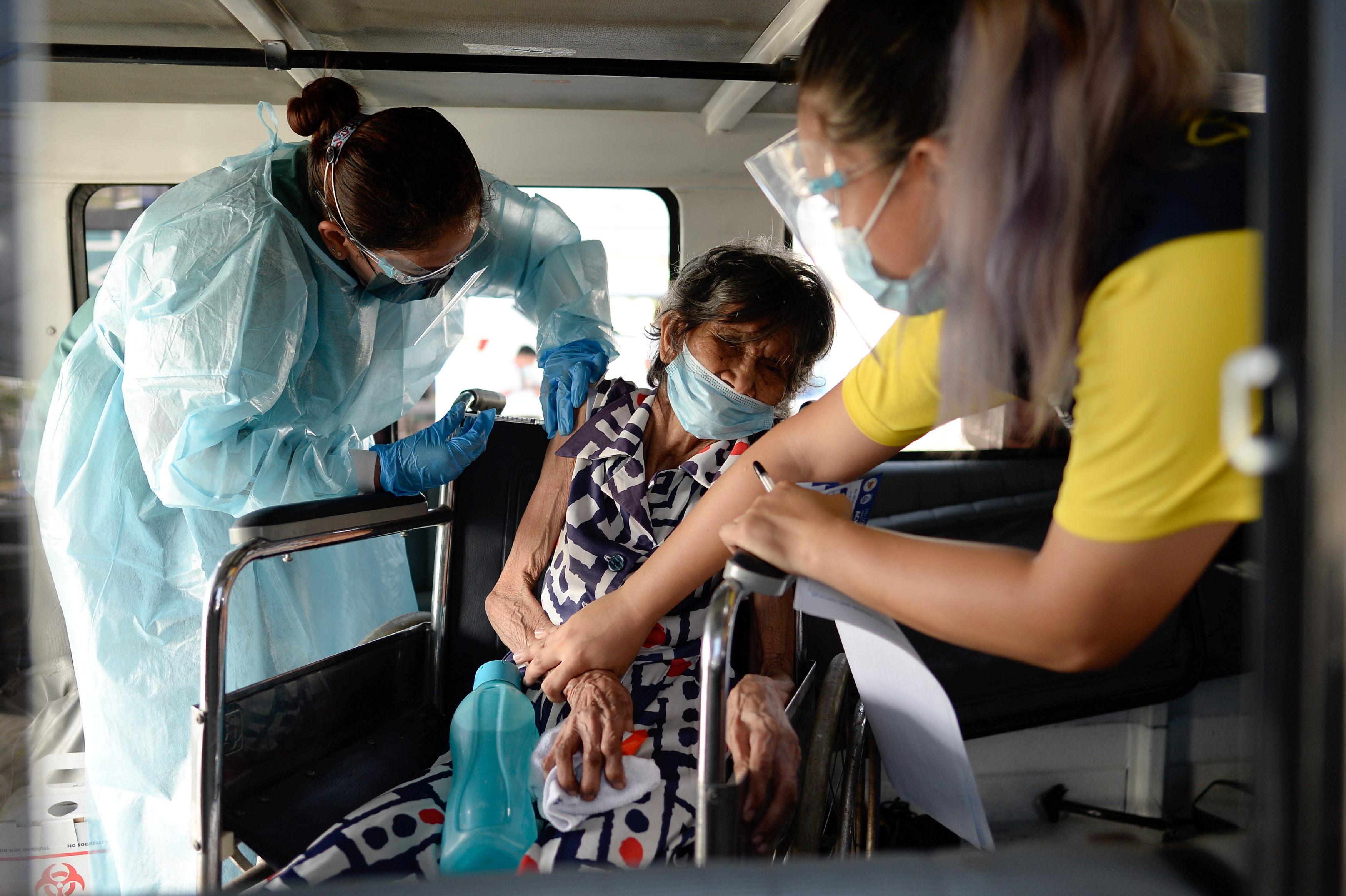 Felipa Tabladillo, 86, receives a dose of China's Sinovac Biotech coronavirus disease (COVID-19) vaccine at a drive-thru vaccination site for bedridden and persons with disabilities, in Makati city, Metro Manila, Philippines, May 7, 2021. REUTERS/Lisa Marie David