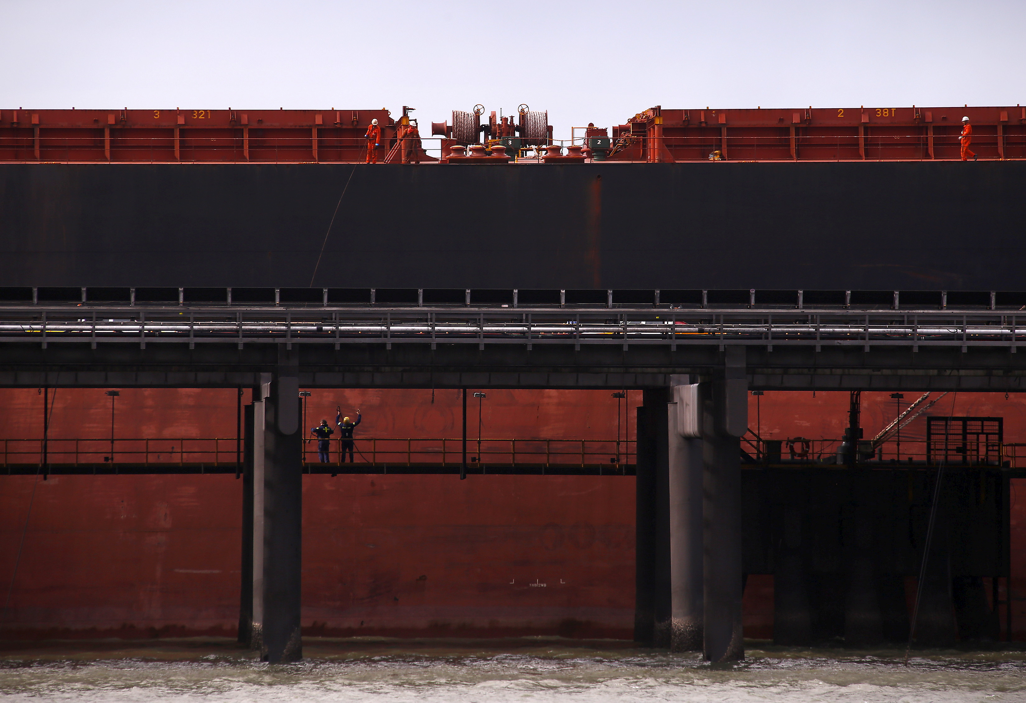 Port workers load a ship with coal at the RG Tanna Coal Terminal located at the town of Gladstone in Queensland, Australia, June 12, 2015.   REUTERS/David Gray/File Photo