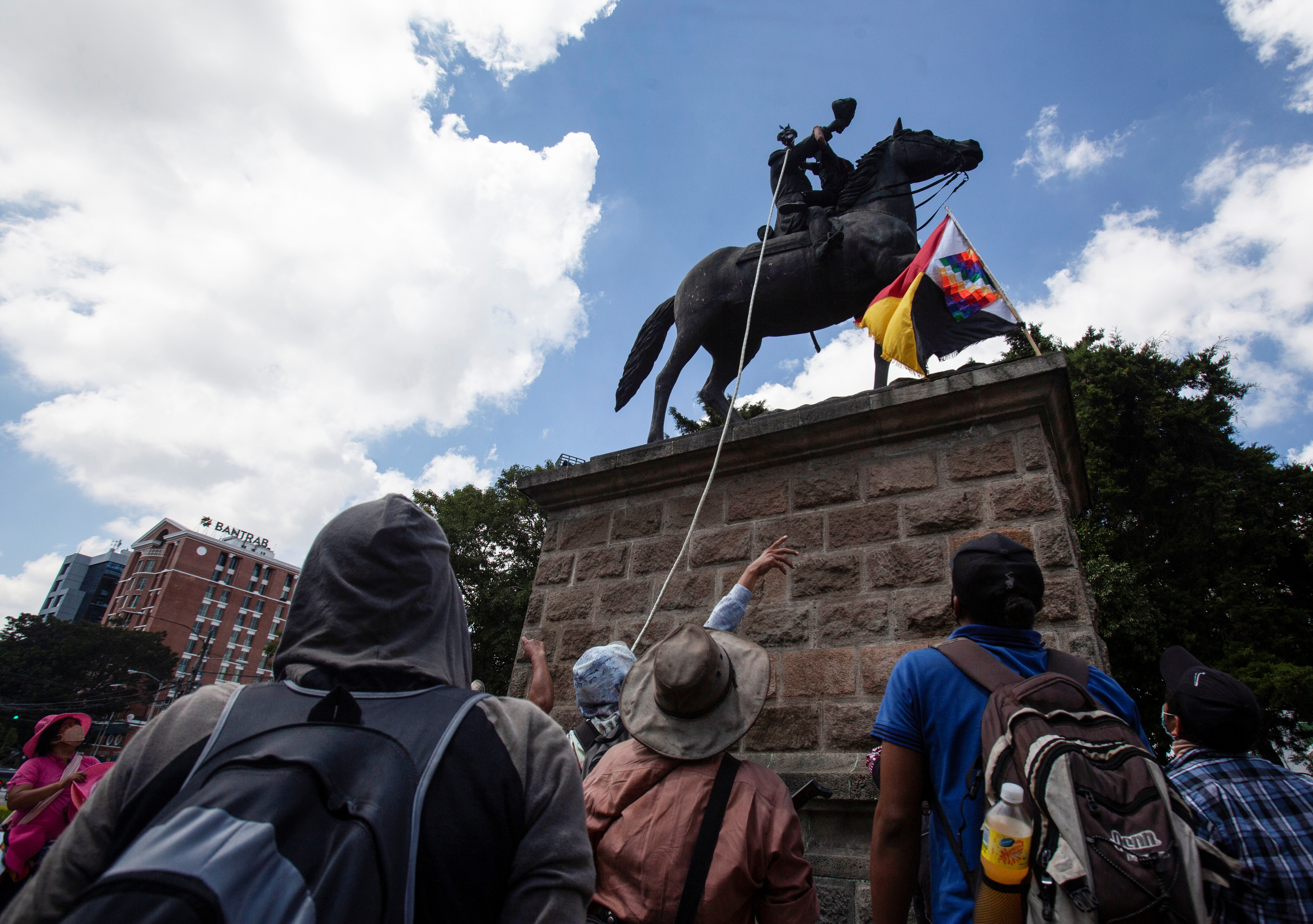 Demonstrators attempt to topple the statue of former President Jose Maria Reina Barrios during protests against the treatment of indigenous people by European conquerors, during Hispanic Heritage Day, in Guatemala City, Guatemala, October 12, 2021. REUTERS/Stringer