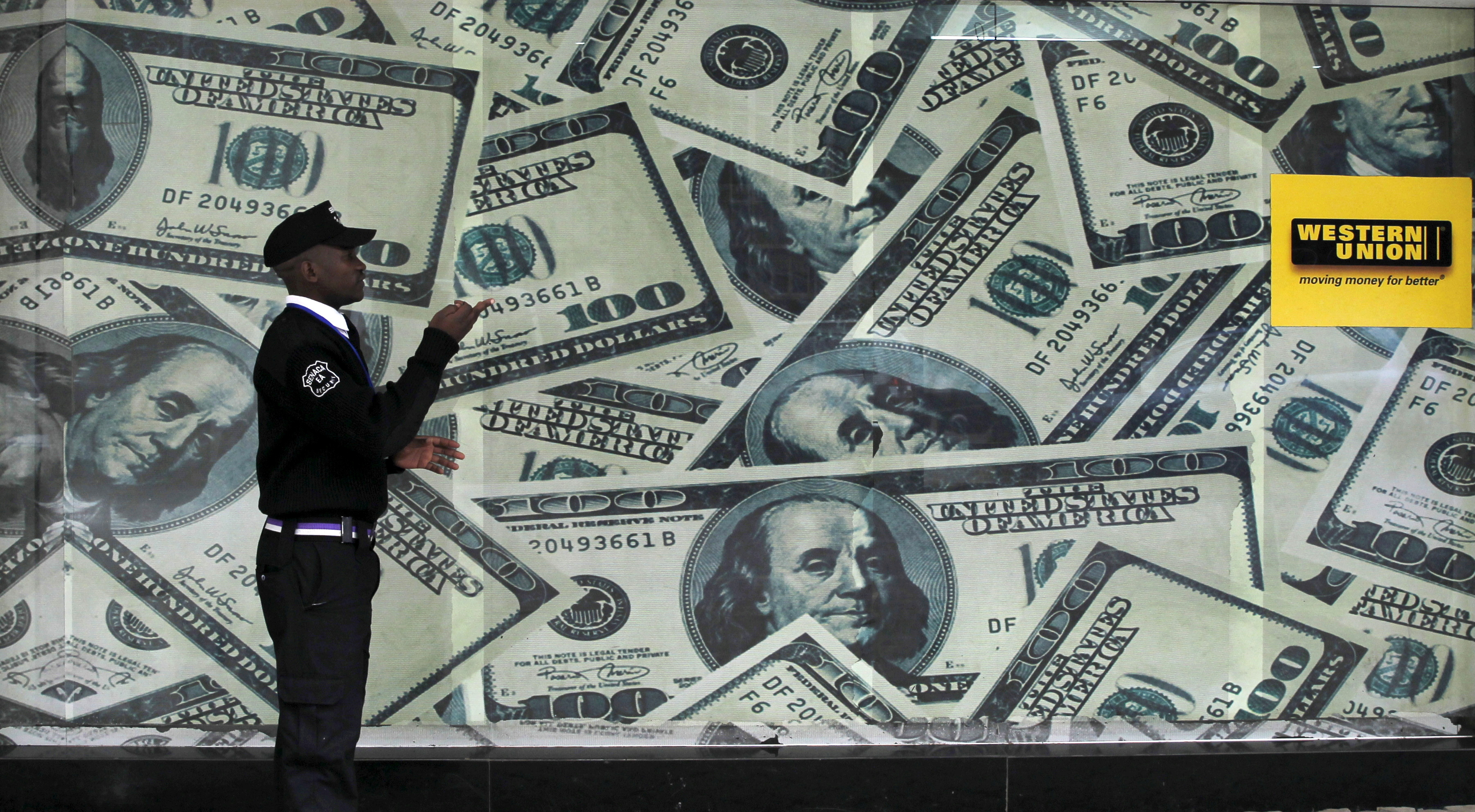 A security guard walks past a montage of old U.S. dollar bills outside a currency exchange in Kenya's capital Nairobi July 23, 2015. REUTERS/Thomas Mukoya/File Photo
