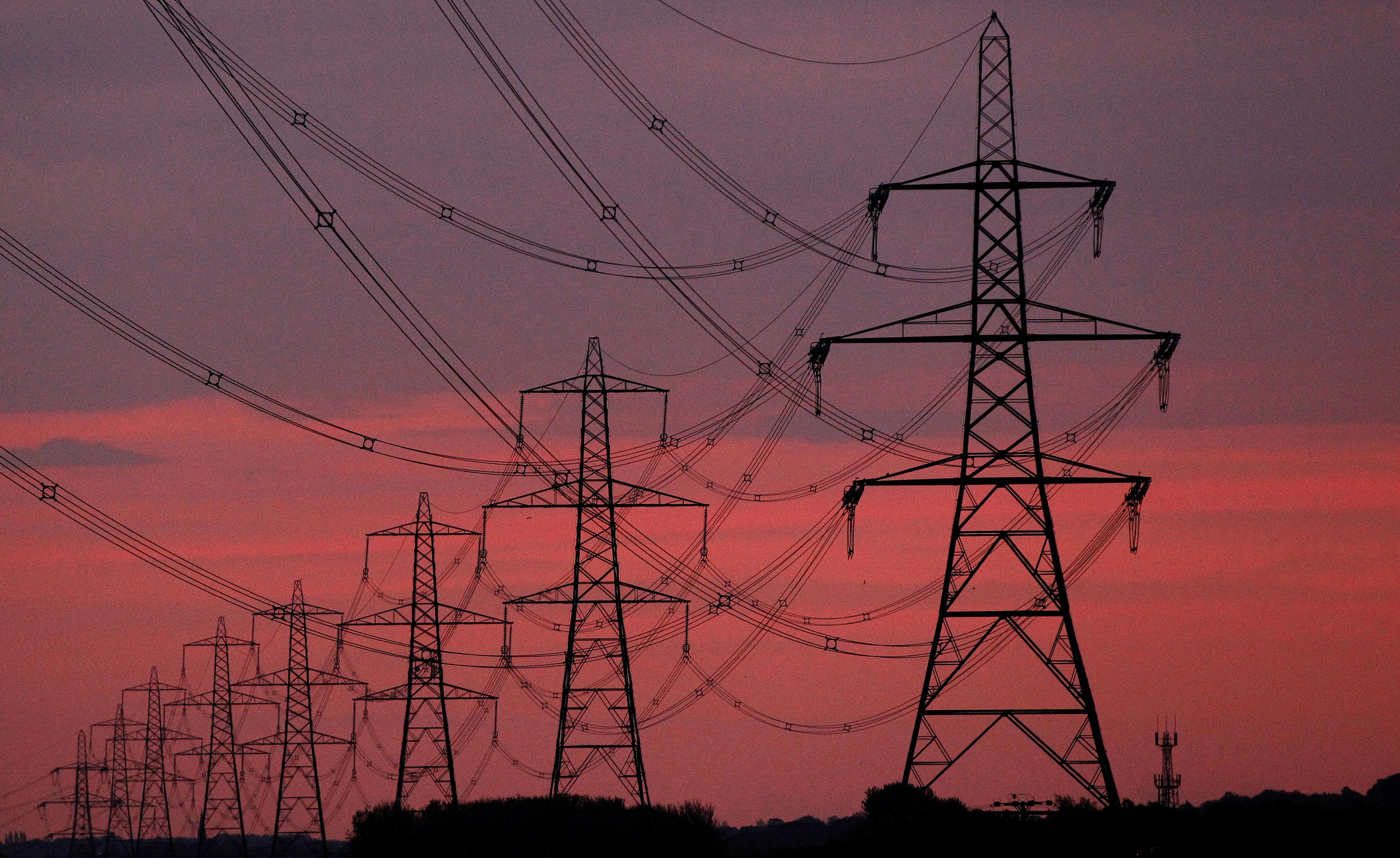 The sun rises behind electricity pylons near Chester, northern England October 24, 2011.  REUTERS/Phil Noble/File Photo