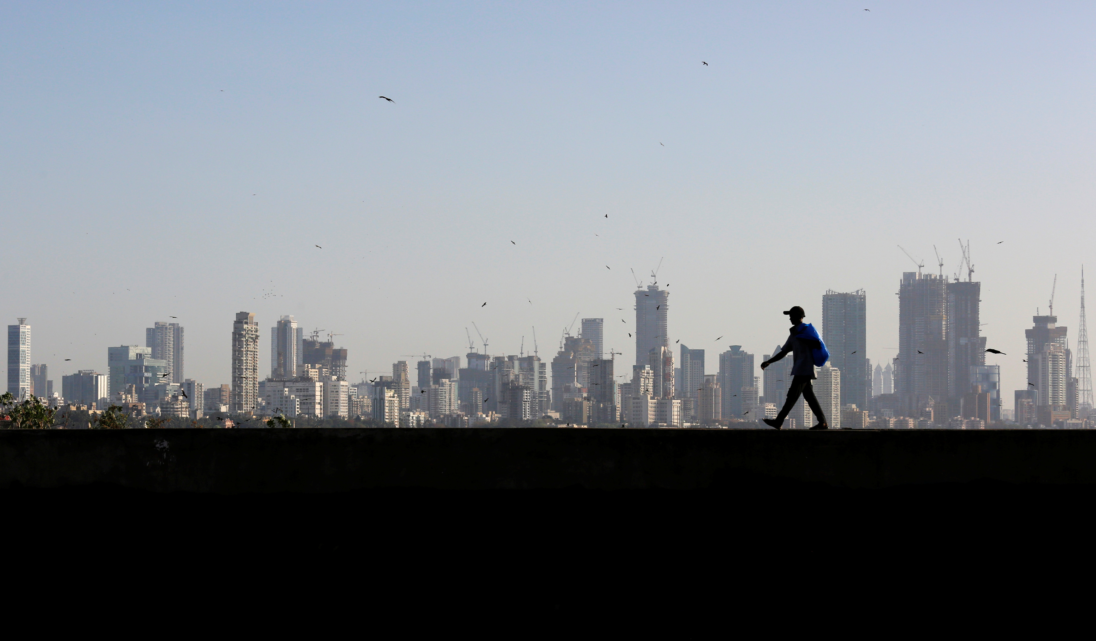 A man walks along a wall overlooking the central Mumbai's financial district skyline, India, March 9, 2017. REUTERS/Danish Siddiqui