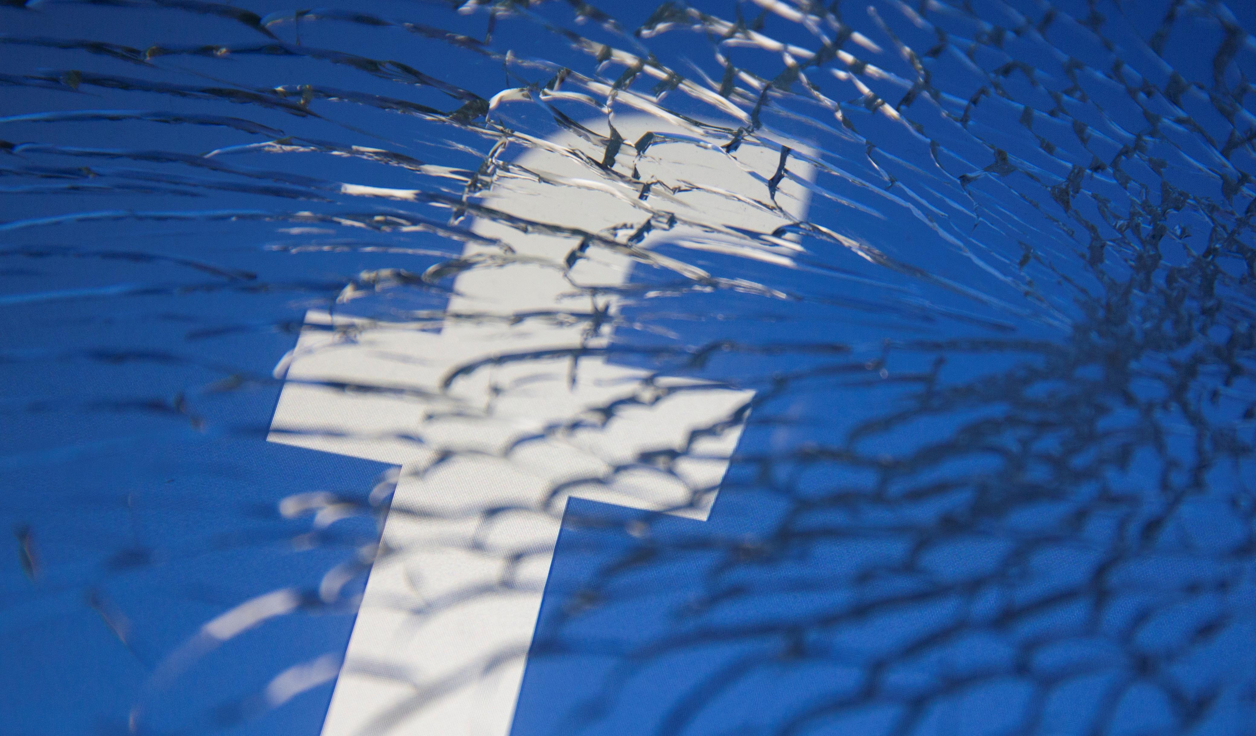 Facebook logo displayed through broken glass in this illustration taken October 4, 2021. REUTERS/Dado Ruvic/Illustration