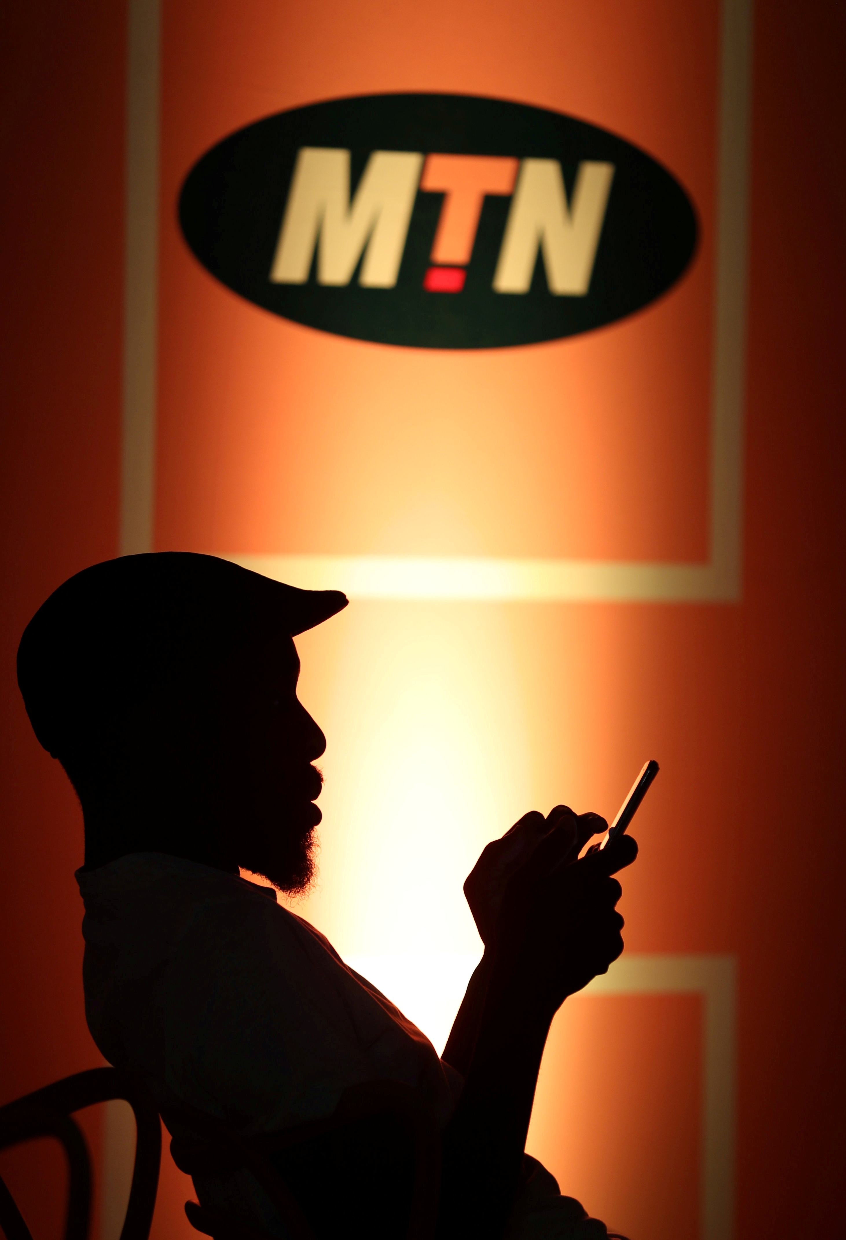 A guest types on his mobile phone as he sits below an MTN logo during the launch of its mobile money service in Johannesburg, South Africa, January 30, 2020. REUTERS/Siphiwe Sibeko