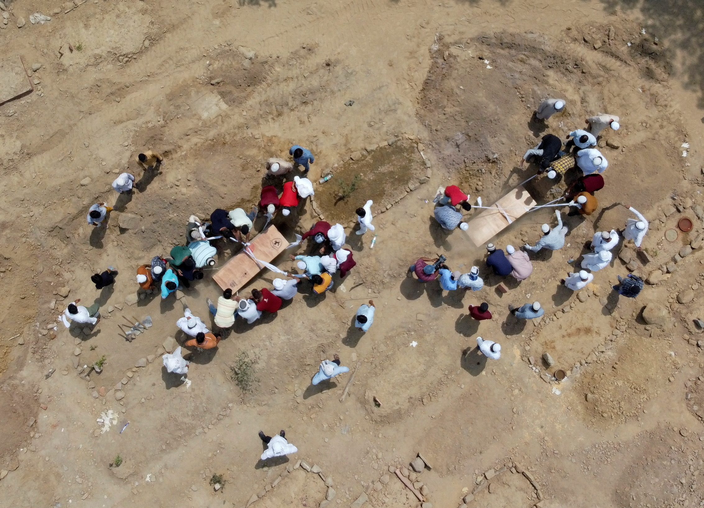 People bury the bodies of victims who died due to the coronavirus disease (COVID-19), at a graveyard in New Delhi, India, April 16, 2021. Picture taken with a drone. REUTERS/Danish Siddiqui