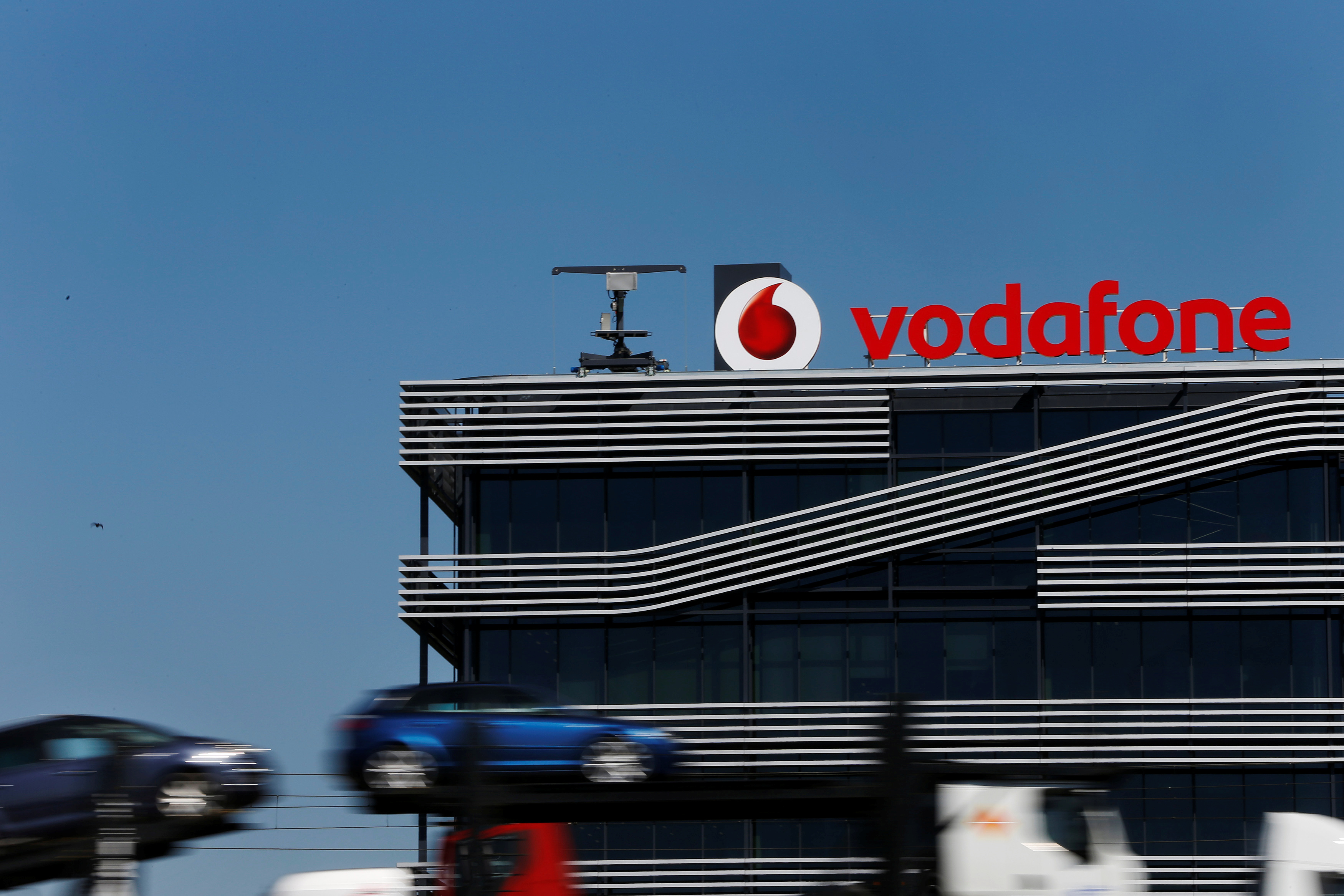 A truck carrying cars speeds past the headquarters of Vodafone in Madrid March 17, 2014. REUTERS/Susana Vera/File Photo