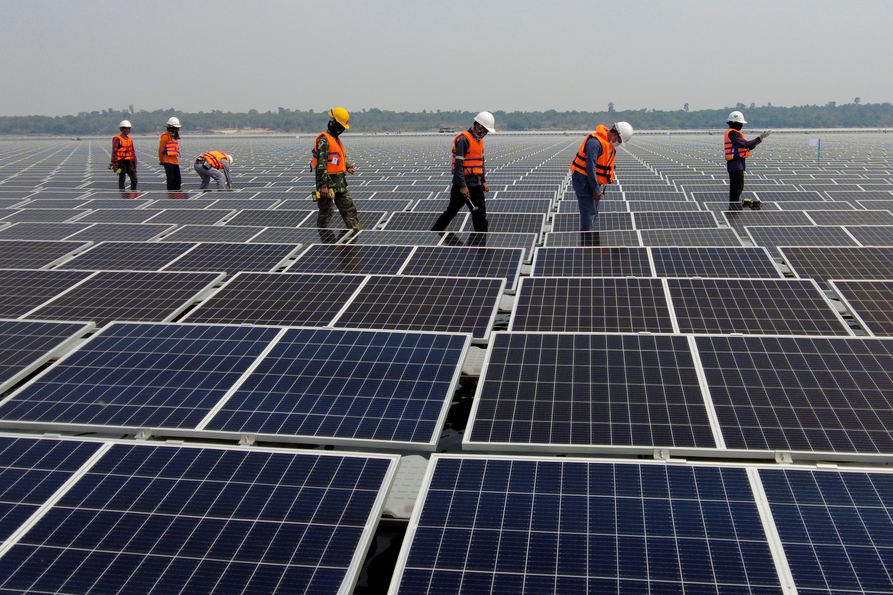 Workers walk between solar cell panels over the water surface of Sirindhorn Dam in Ubon Ratchathani, Thailand April 8, 2021. Picture taken April 8, 2021 with a drone. REUTERS/Prapan Chankaew