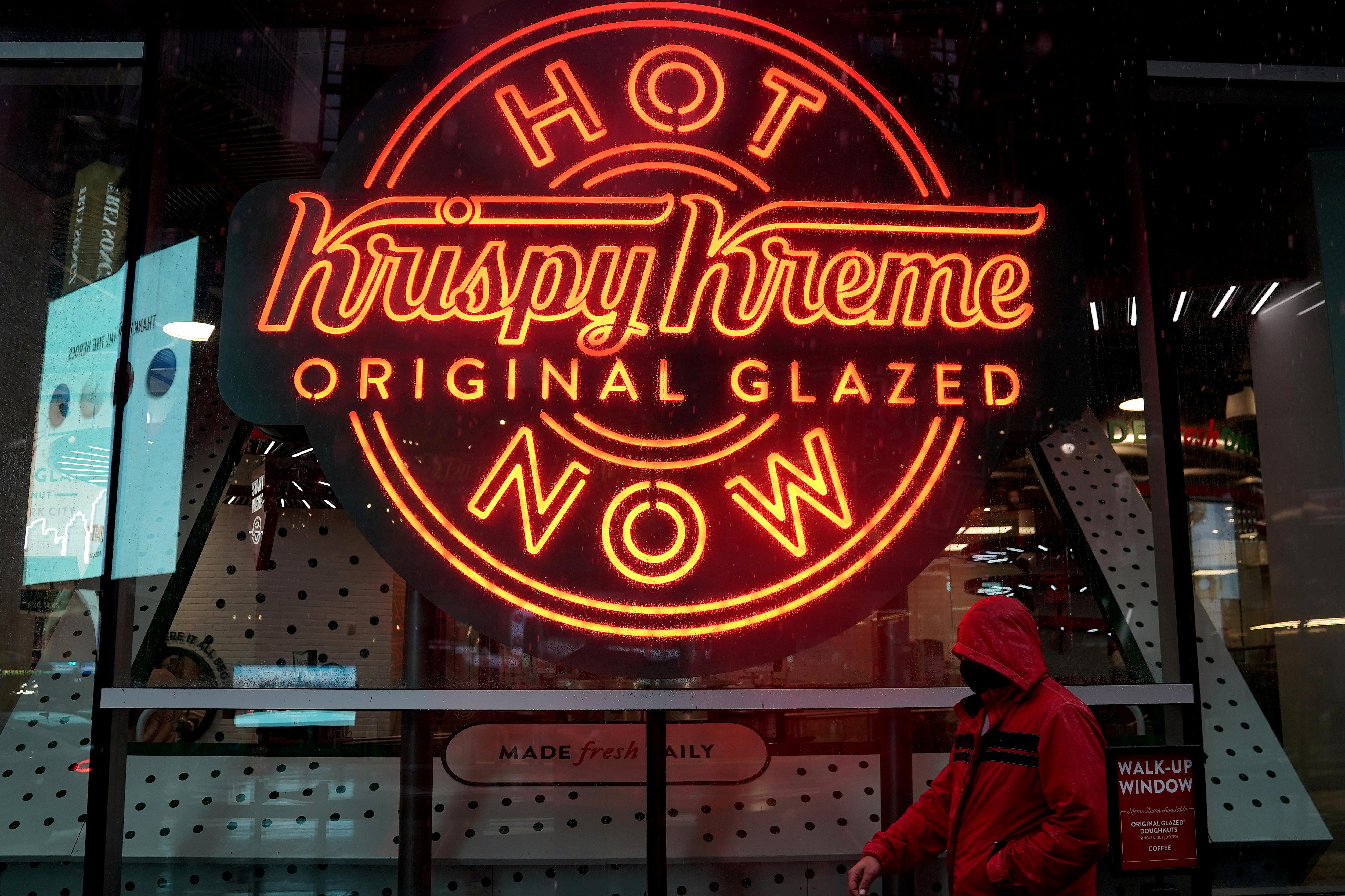 A man walks past a Krispy Kreme