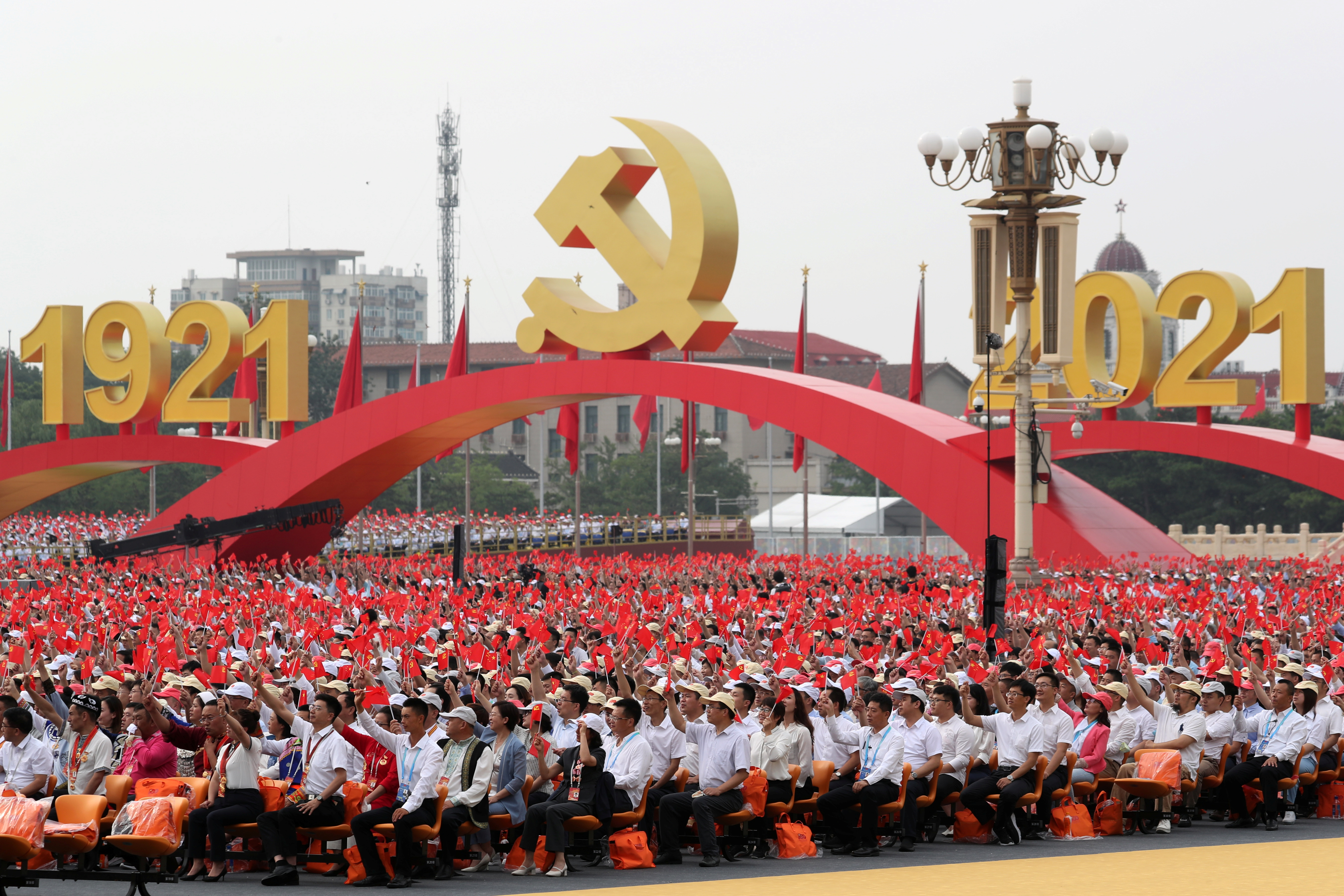 Participants wave national and party flags before the event marking the 100th founding anniversary of the Communist Party of China, on Tiananmen Square in Beijing, China July 1, 2021. REUTERS/Carlos Garcia Rawlins