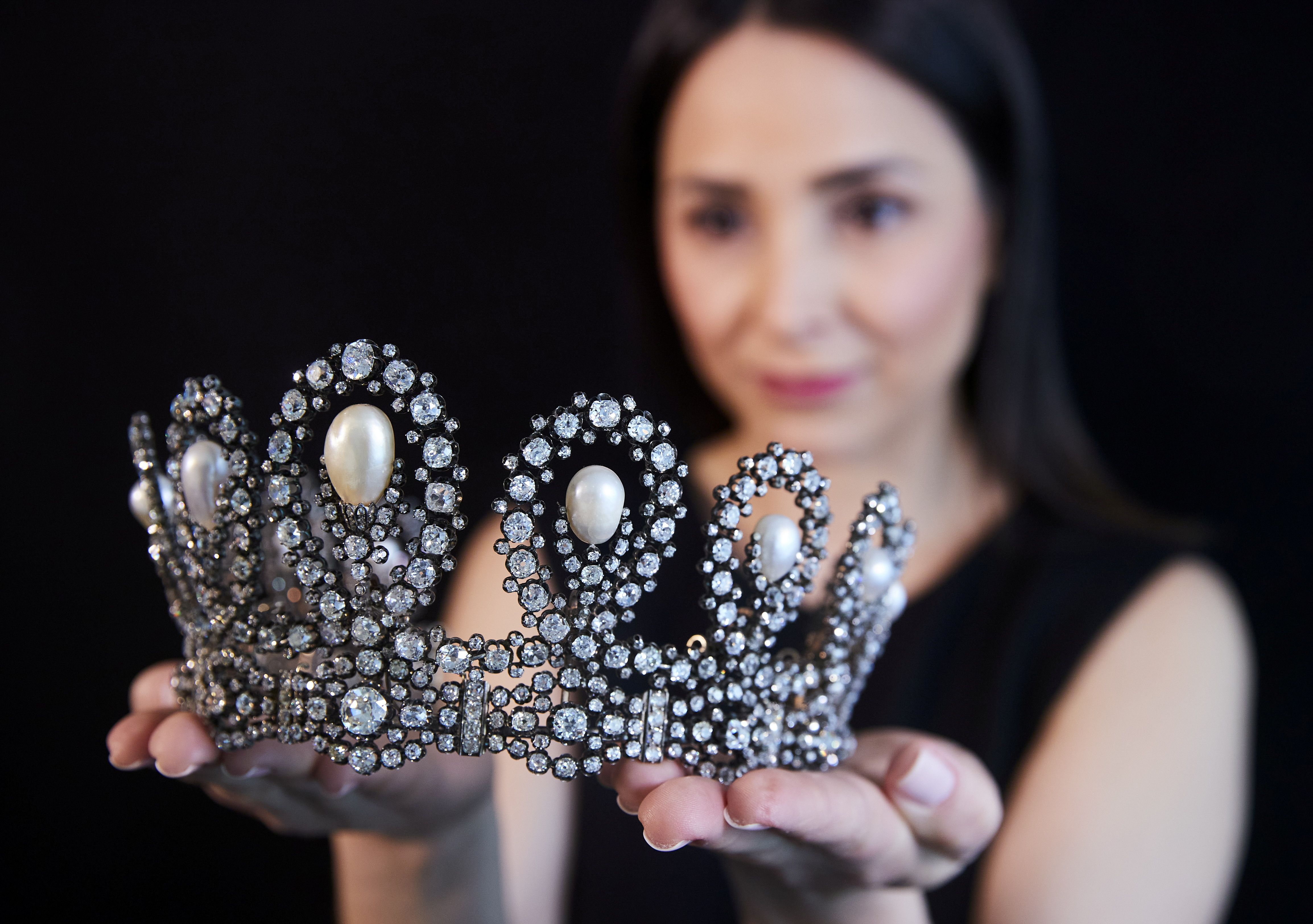 A staff holds a diamond and pearl tiara passed down through generations of the Italian royal family during a preview at Sotheby's before their auction in Geneva, Switzerland, May 6, 2021.  REUTERS/Denis Balibouse