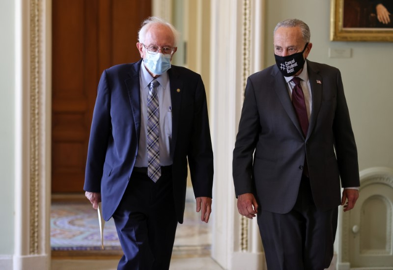 Senate Majority leader Chuck Schumer (D-NY) and Senator Bernie Sanders (D-VT) walk together as the Senate continues to work through the bipartisan infrastructure bill, at the United States Capitol in Washington, U.S., August 9, 2021. REUTERS/Evelyn Hockstein