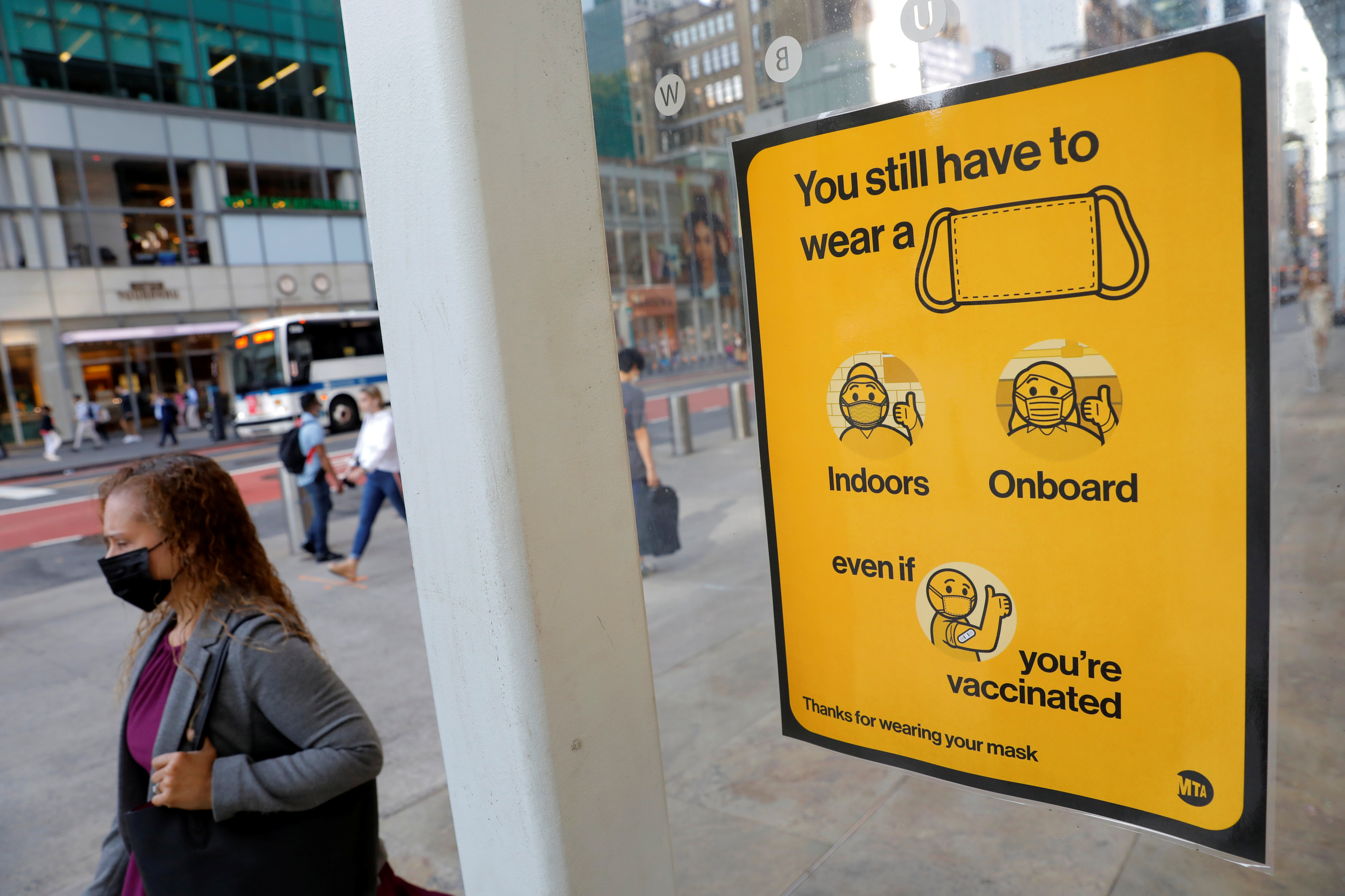 A poster alerting for the wearing of masks is seen on a 42nd Street subway entrance as cases of the infectious coronavirus Delta variant continue to rise in New York City, August 2, 2021. REUTERS/Andrew Kelly