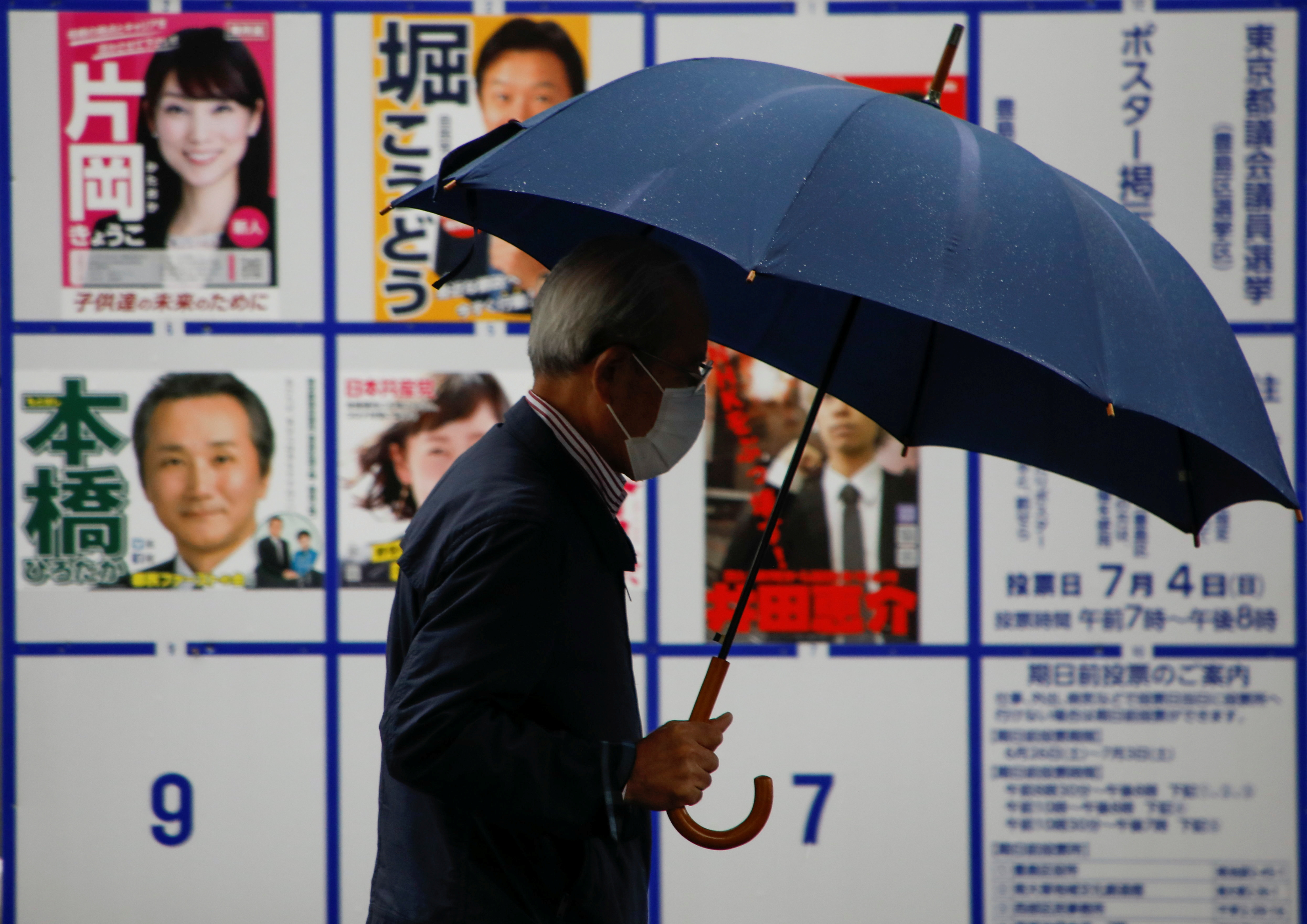 A voter wearing a protective face mask walks past a board displaying posters of candidates for the Tokyo Metropolitan Assembly election near a polling station, amid the coronavirus disease (COVID-19) outbreak, in Tokyo, Japan July 4, 2021.  REUTERS/Issei Kato