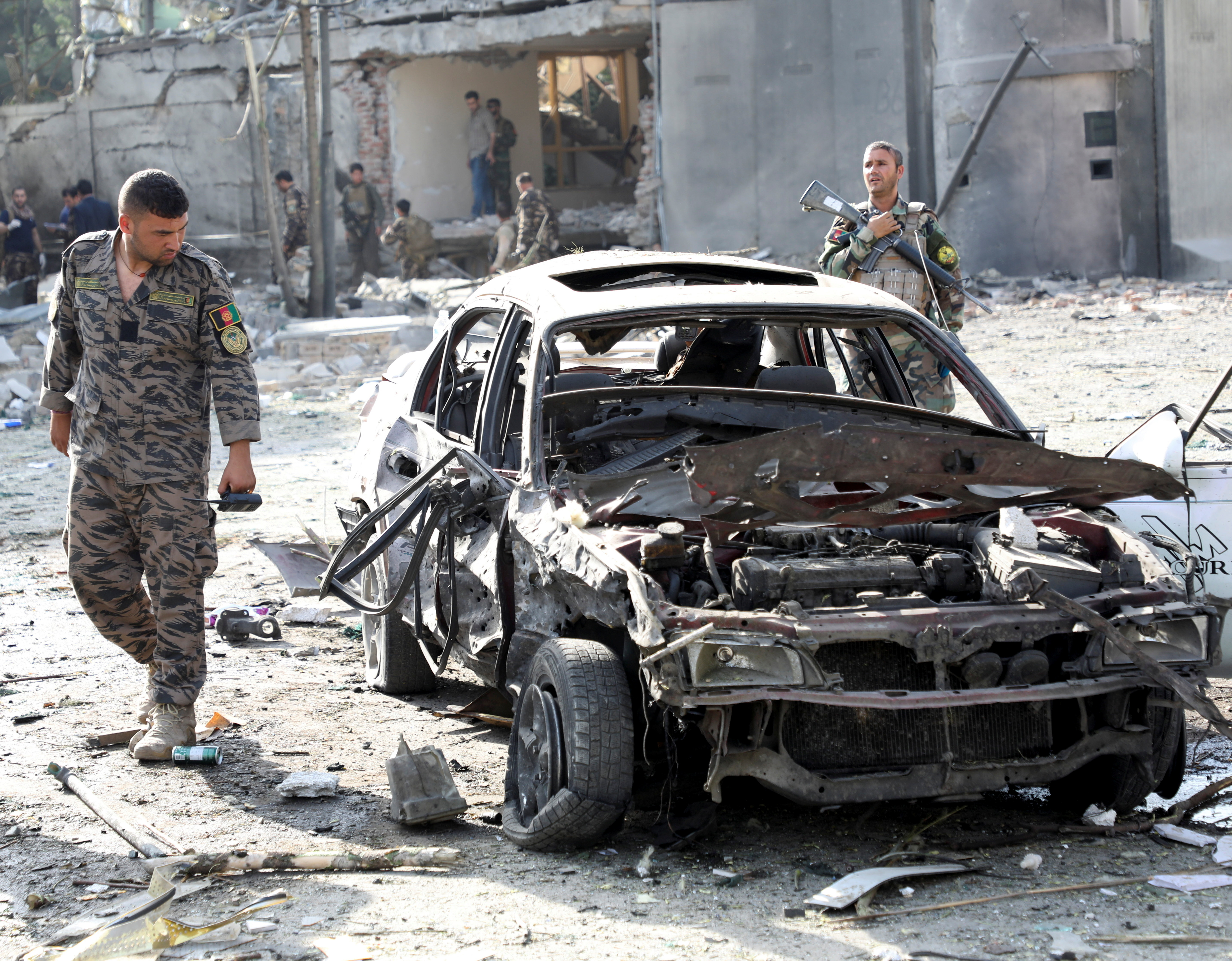 A member of Afghan security forces looks at a damaged car at the site of yesterday's night-time car bomb blast in Kabul, Afghanistan August 4, 2021.REUTERS/Stringer