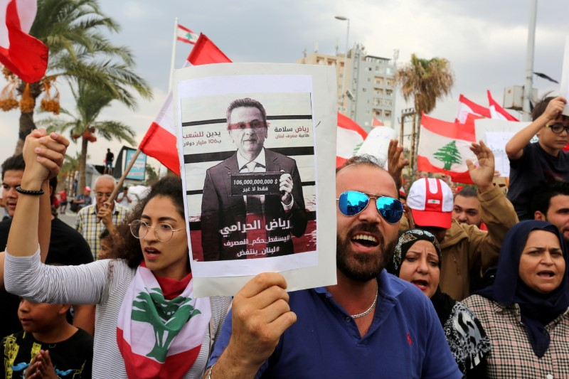 Demonstrators carry Lebanese flags and a banner depicting Lebanon's Central Bank Governor Riad Salameh as they head towards the central bank building during an anti-government protest in the southern city of Tyre, Lebanon October 23, 2019. REUTERS/Aziz Taher/File Photo