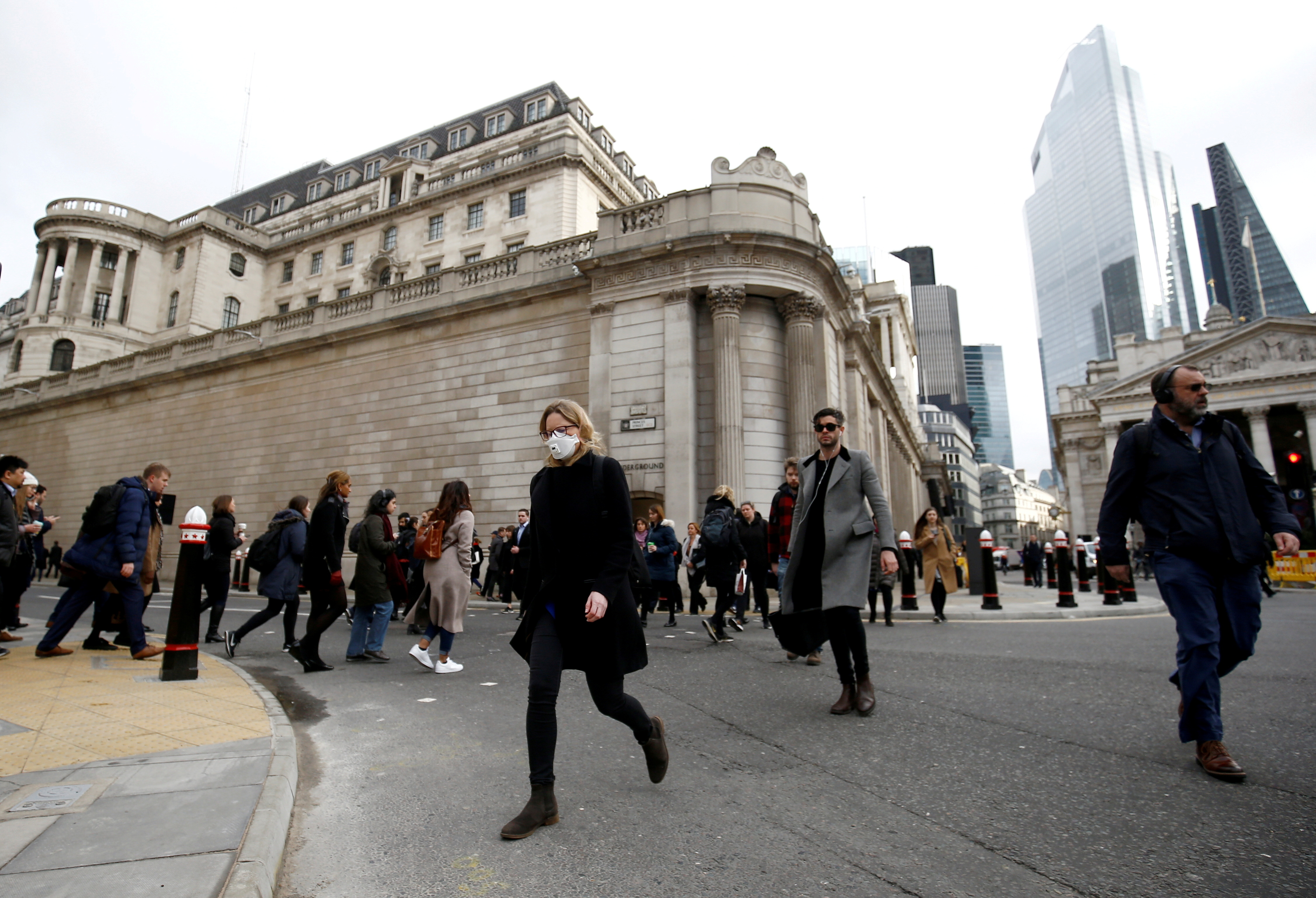 A woman wearing a protective face mask, following an outbreak of the coronavirus, walks in front of the Bank of England in London, Britain March 11, 2020. REUTERS/Henry Nicholls