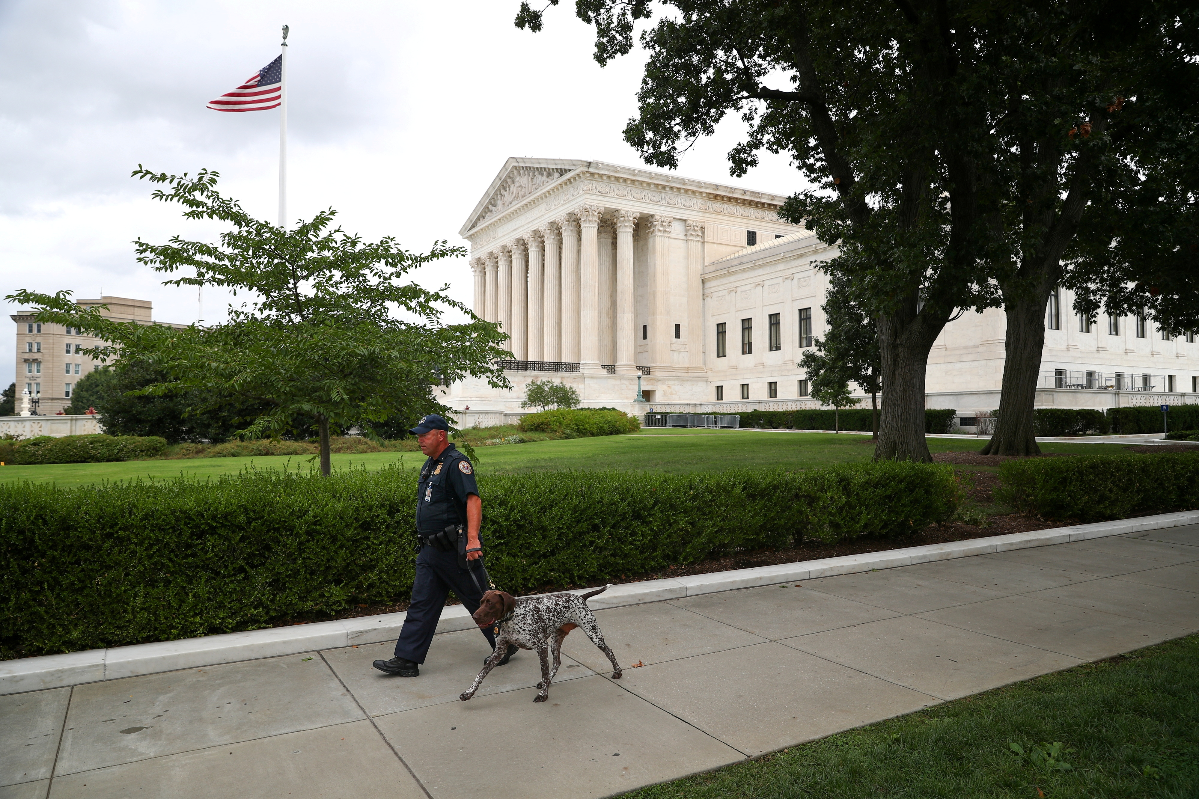 A U.S. Capitol Police Officer walks with a dog near the U.S. Supreme Court in Washington, U.S., September 1, 2021. REUTERS/Tom Brenner/File Photo