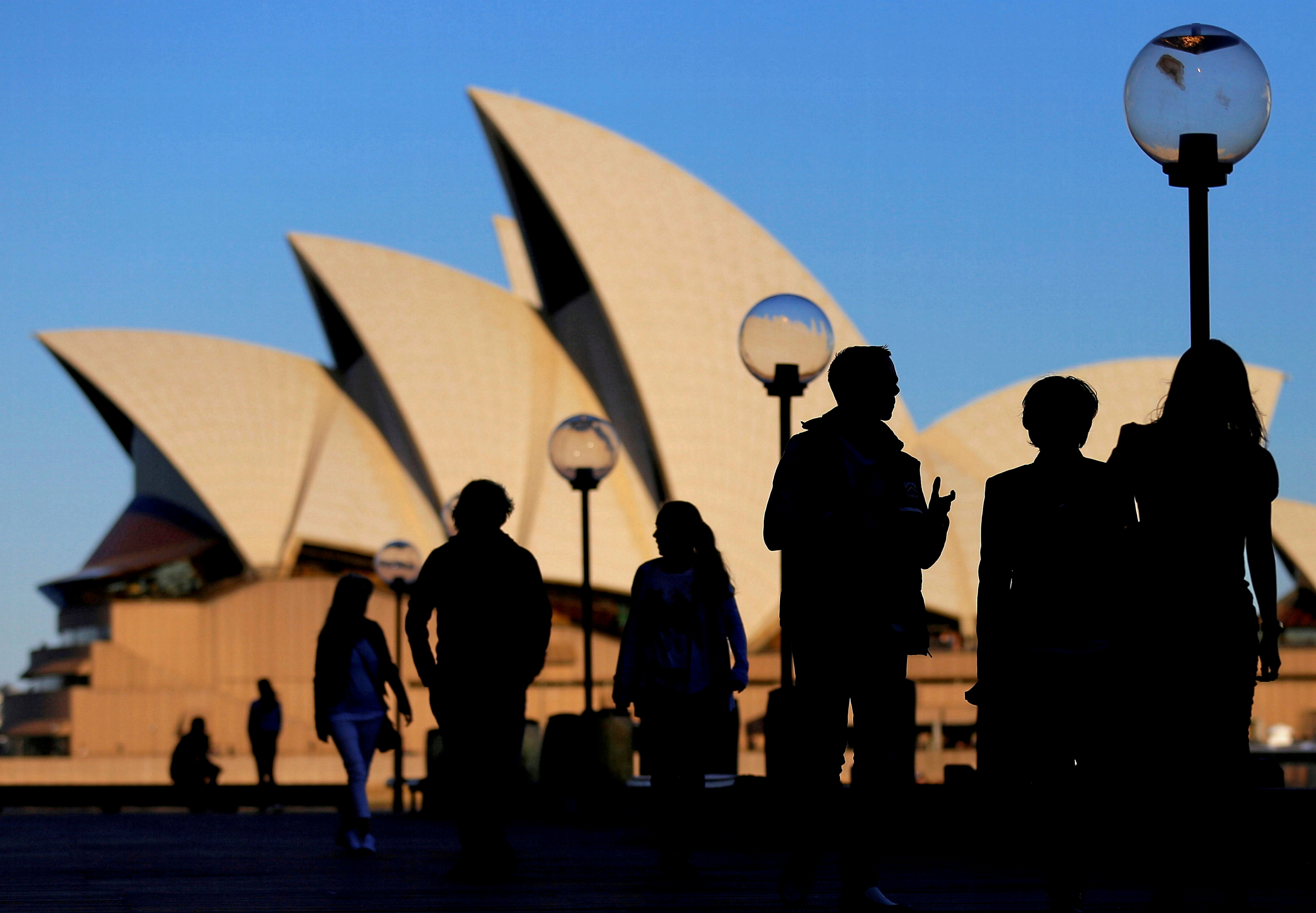 People are silhouetted against the Sydney Opera House at sunset in Australia, November 2, 2016. REUTERS/Steven Saphore