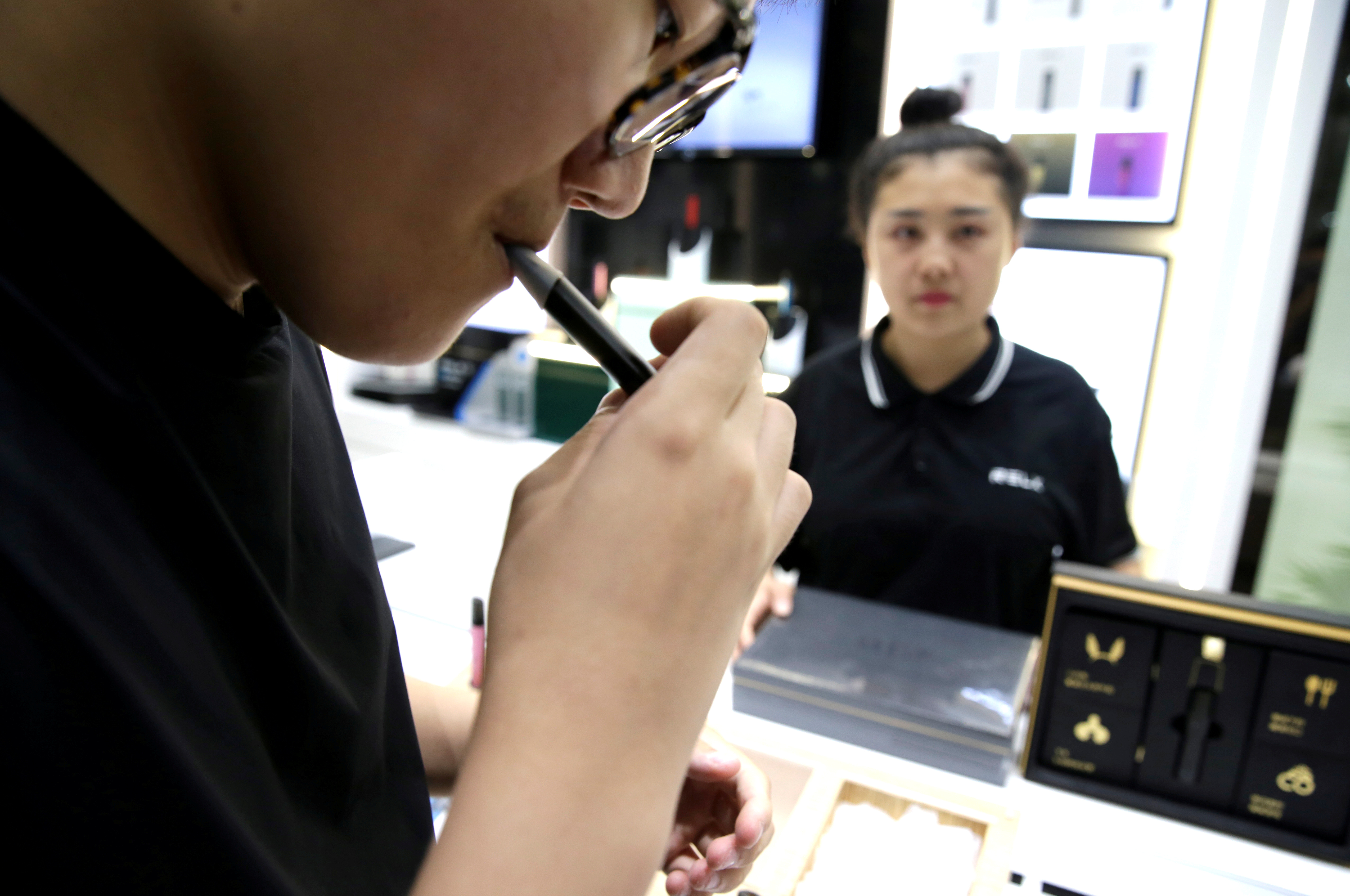A customer tries a Relx e-cigarette at its flagship store in Beijing, China, August 2, 2019. REUTERS/Jason Lee/File Photo