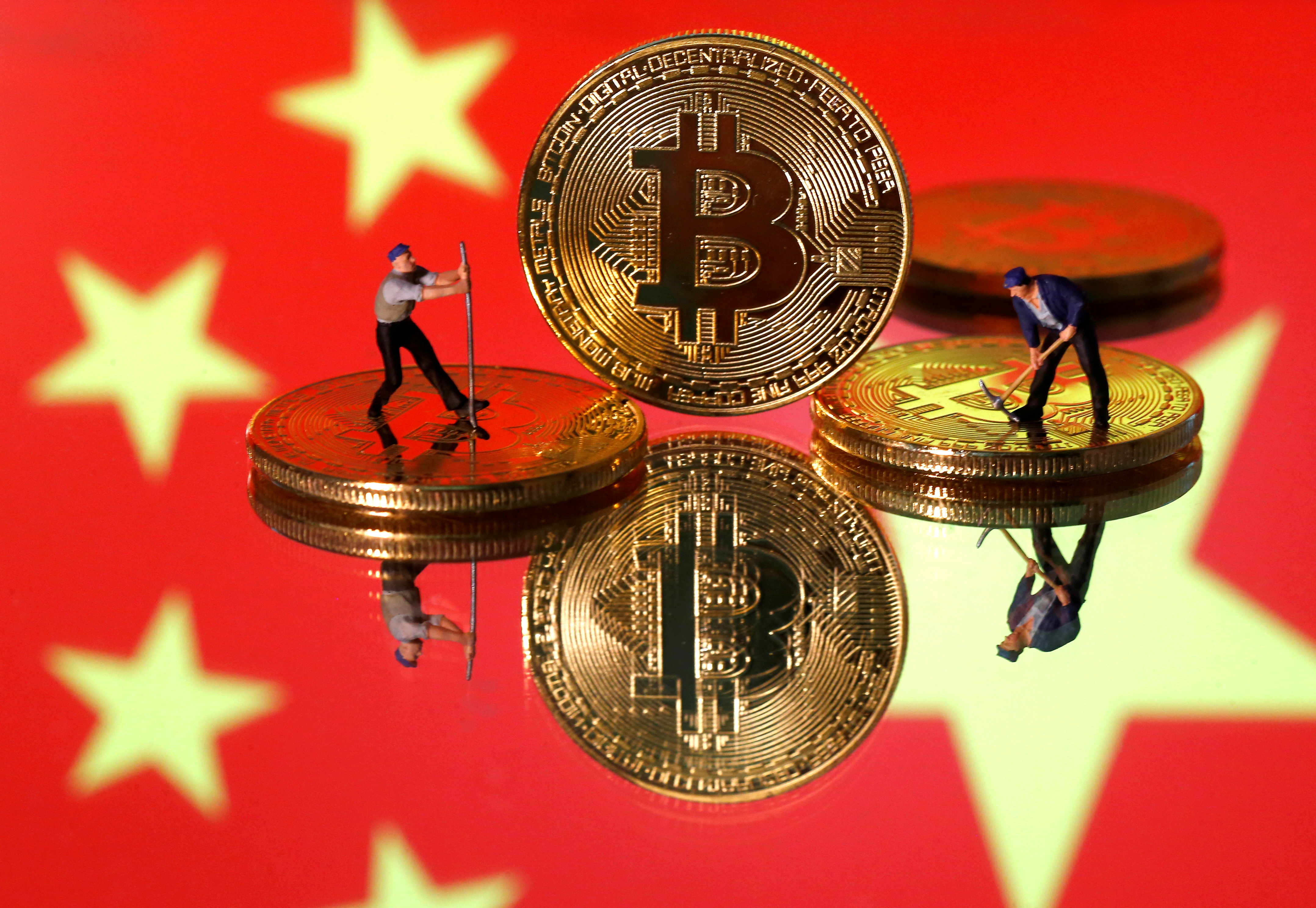 Small toy figurines are seen on representations of the Bitcoin virtual currency displayed in front of an image of China's flag in this illustration picture, April 9, 2019. REUTERS/Dado Ruvic/Illustration/File Photo