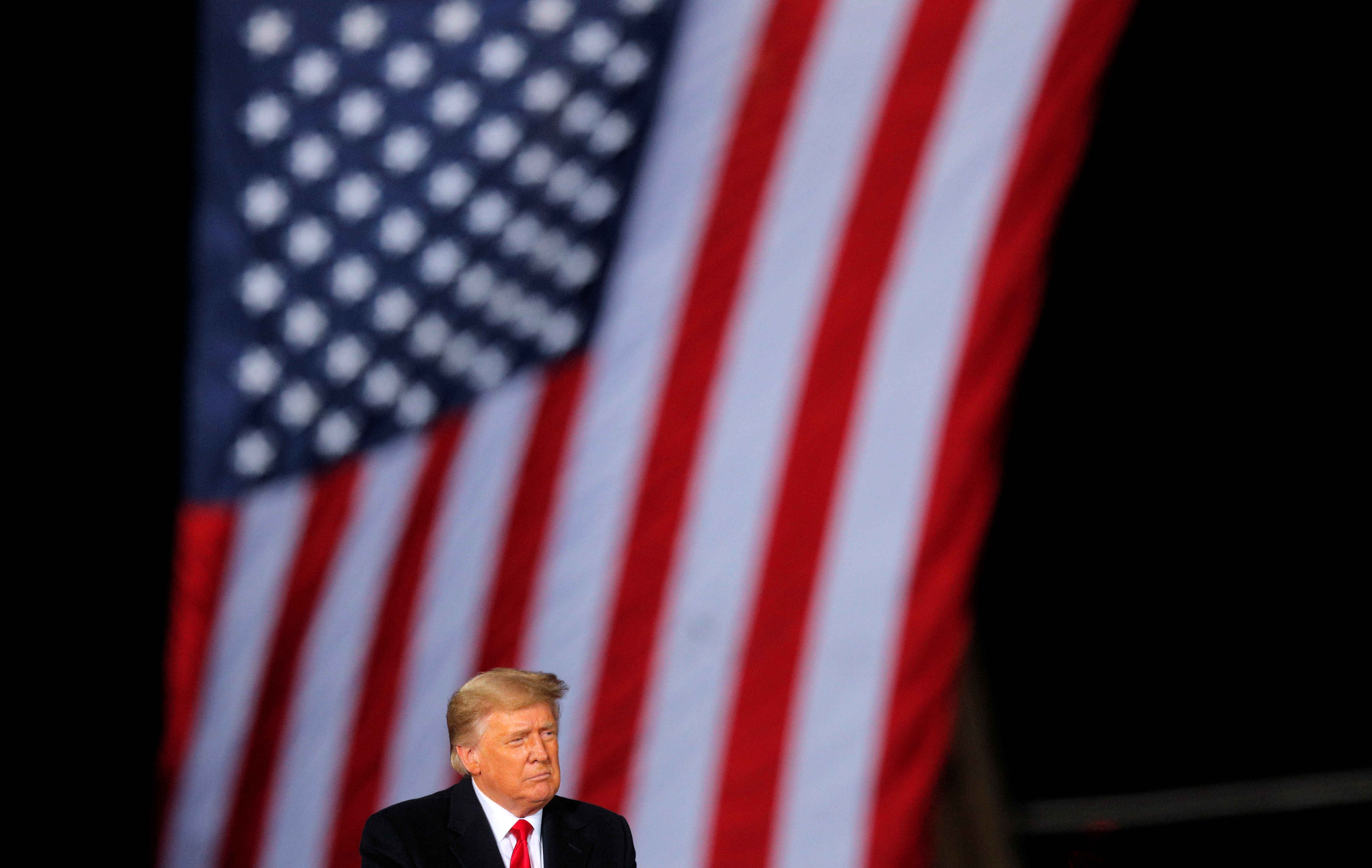 U.S. President Donald Trump is seen in front of a U.S. flag while campaigning for Republican Senator Kelly Loeffler on the eve of the run-off election to decide both of Georgia's Senate seats, in Dalton, Georgia, U.S., January 4, 2021. REUTERS/Brian Snyder/File Photo