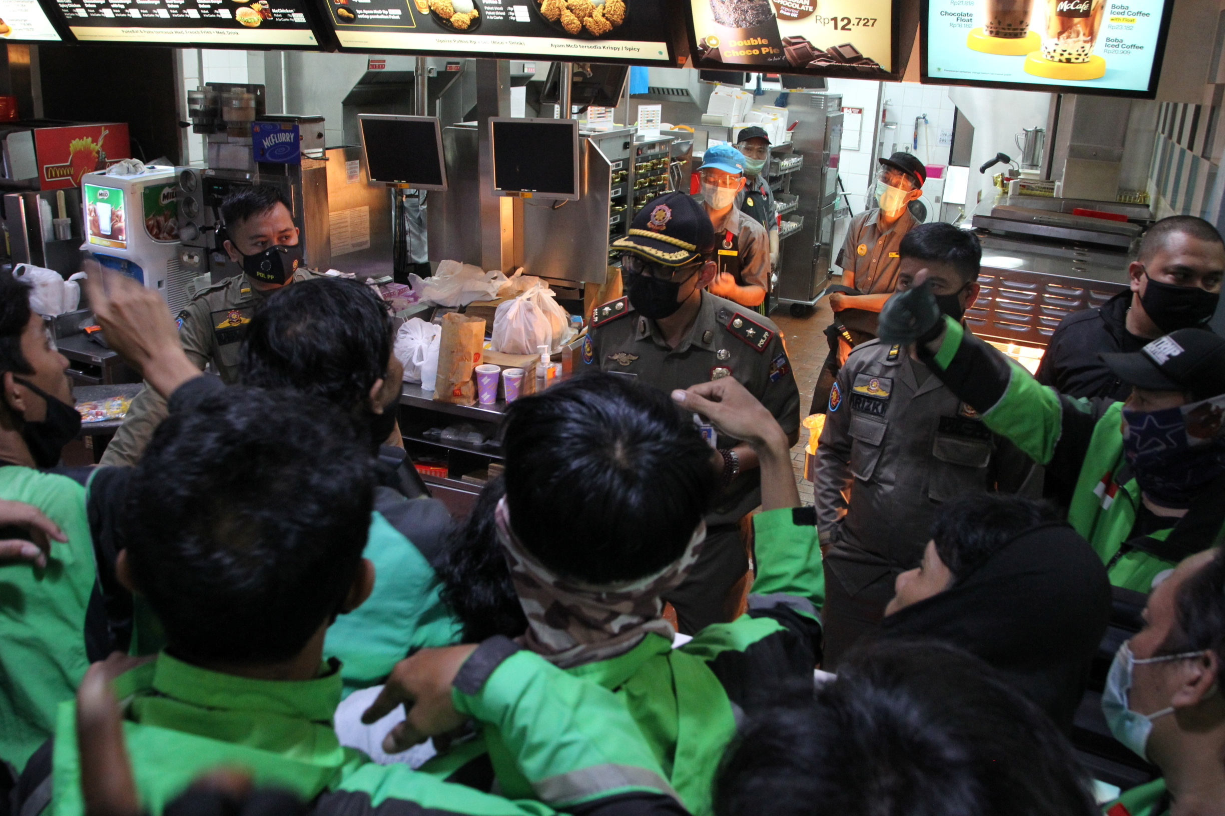 Food delivery drivers crowd in a McDonald's restaurant and wait for BTS meal orders in Bogor, Indonesia, June 9, 2021 in this picture obtained from social media. SOFYAN SHAH RADAR BOGOR/via REUTERS
