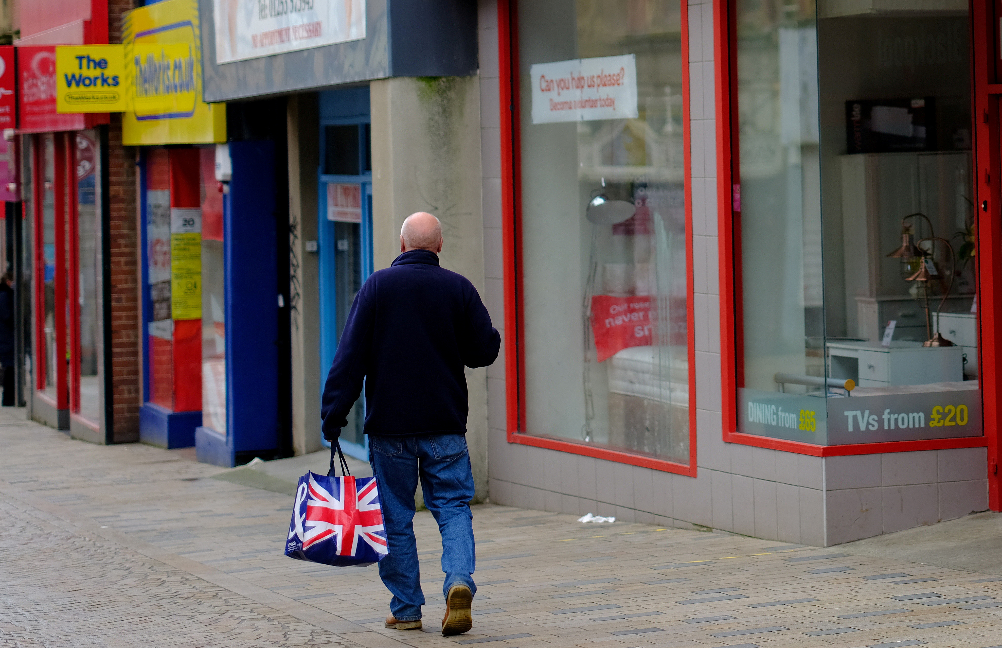 A man carries a Union Jack themed shopping bag as he walks along an empty shopping street in Blackpool, Britain, March 9, 2021. REUTERS/Phil Noble/File Photo