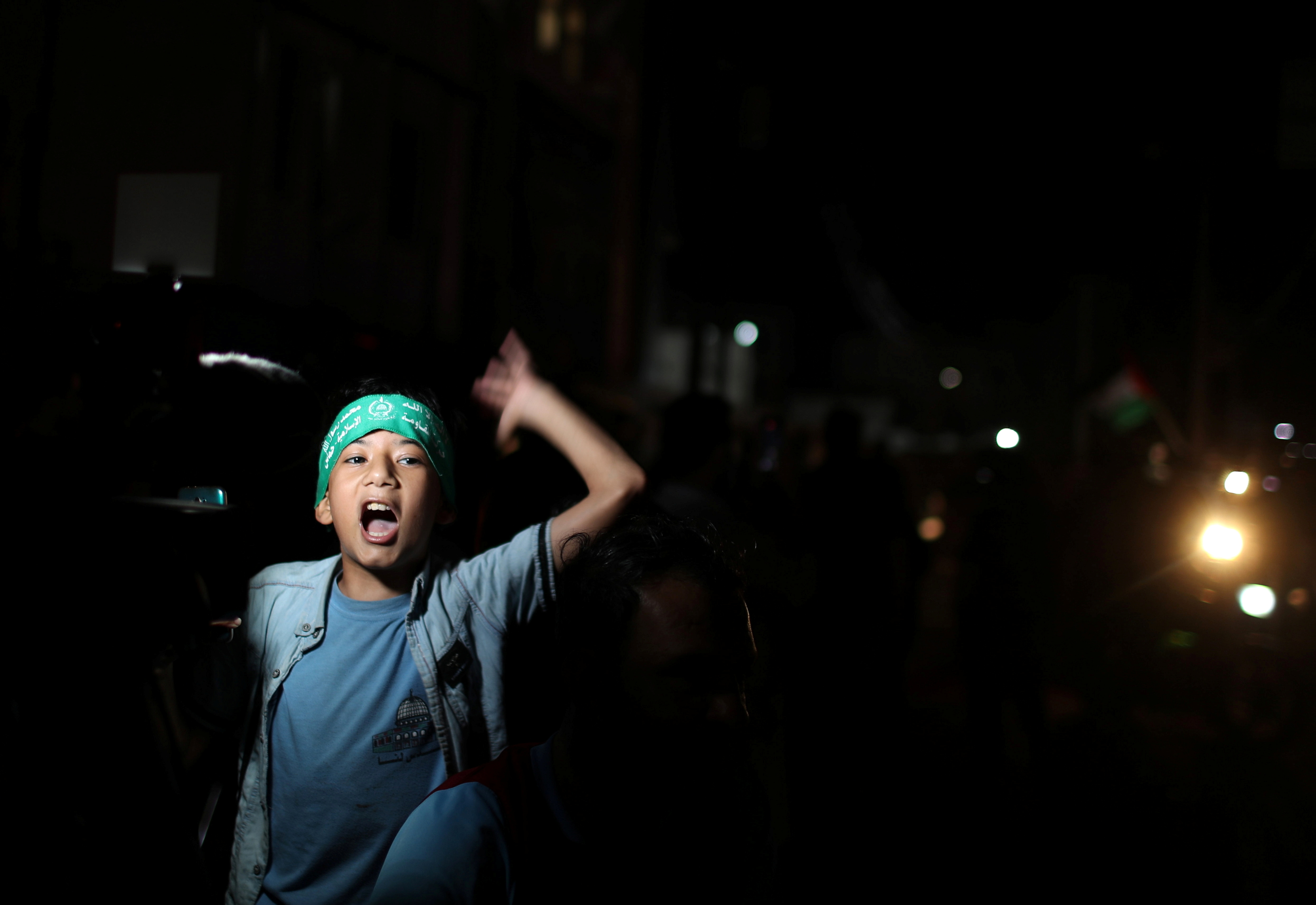 A boy gestures as Palestinians celebrate in the streets following a ceasefire, in Gaza City May 21, 2021. REUTERS/Mohammed Salem