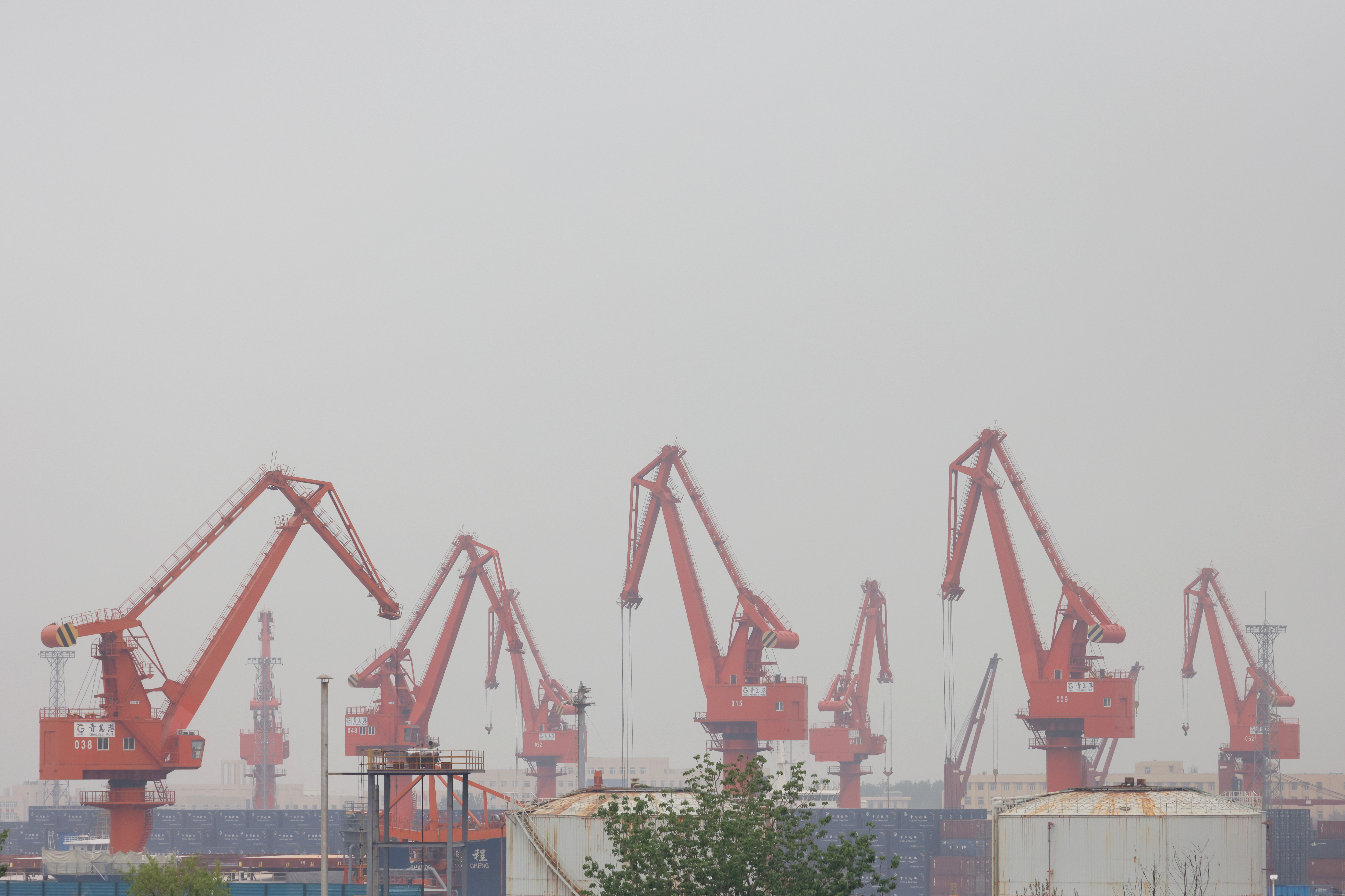 Cranes are seen at the port of Qingdao in Shandong province, China, following an oil spill in the Yellow Sea caused by a collision between tanker A Symphony and bulk vessel Sea Justice off the port, April 28, 2021. REUTERS/Carlos Garcia Rawlins