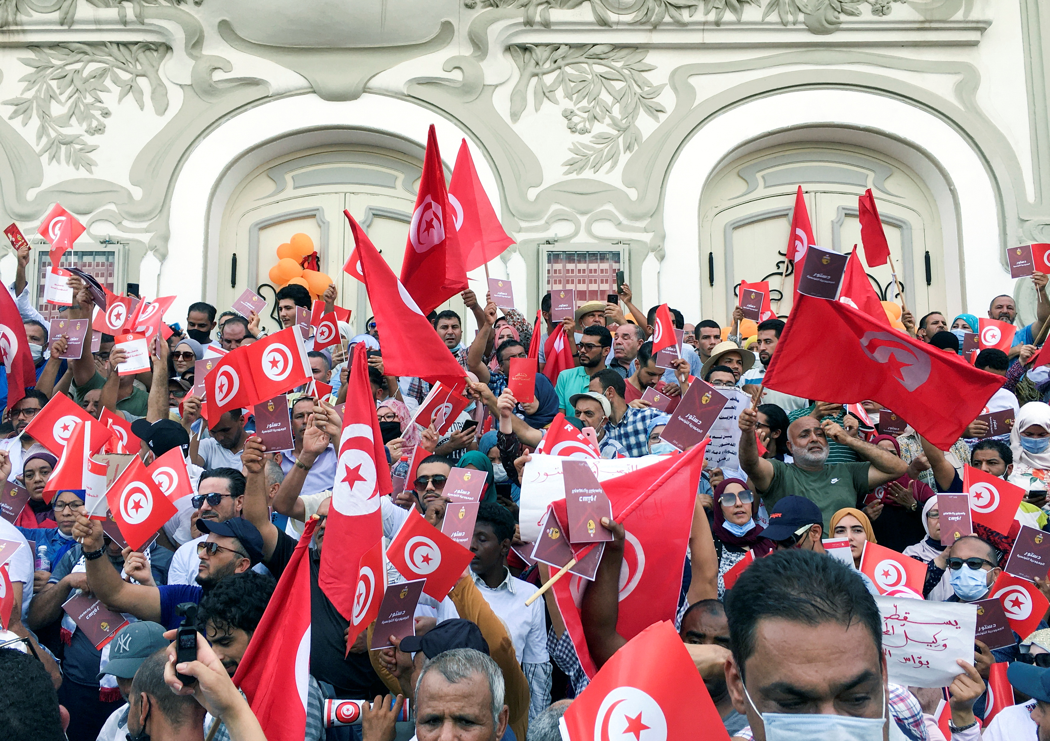 Demonstrators carry flags during a protest against Tunisian President Kais Saied's seizure of governing powers, in Tunis, Tunisia, September 26, 2021. REUTERS/Zoubeir Souissi